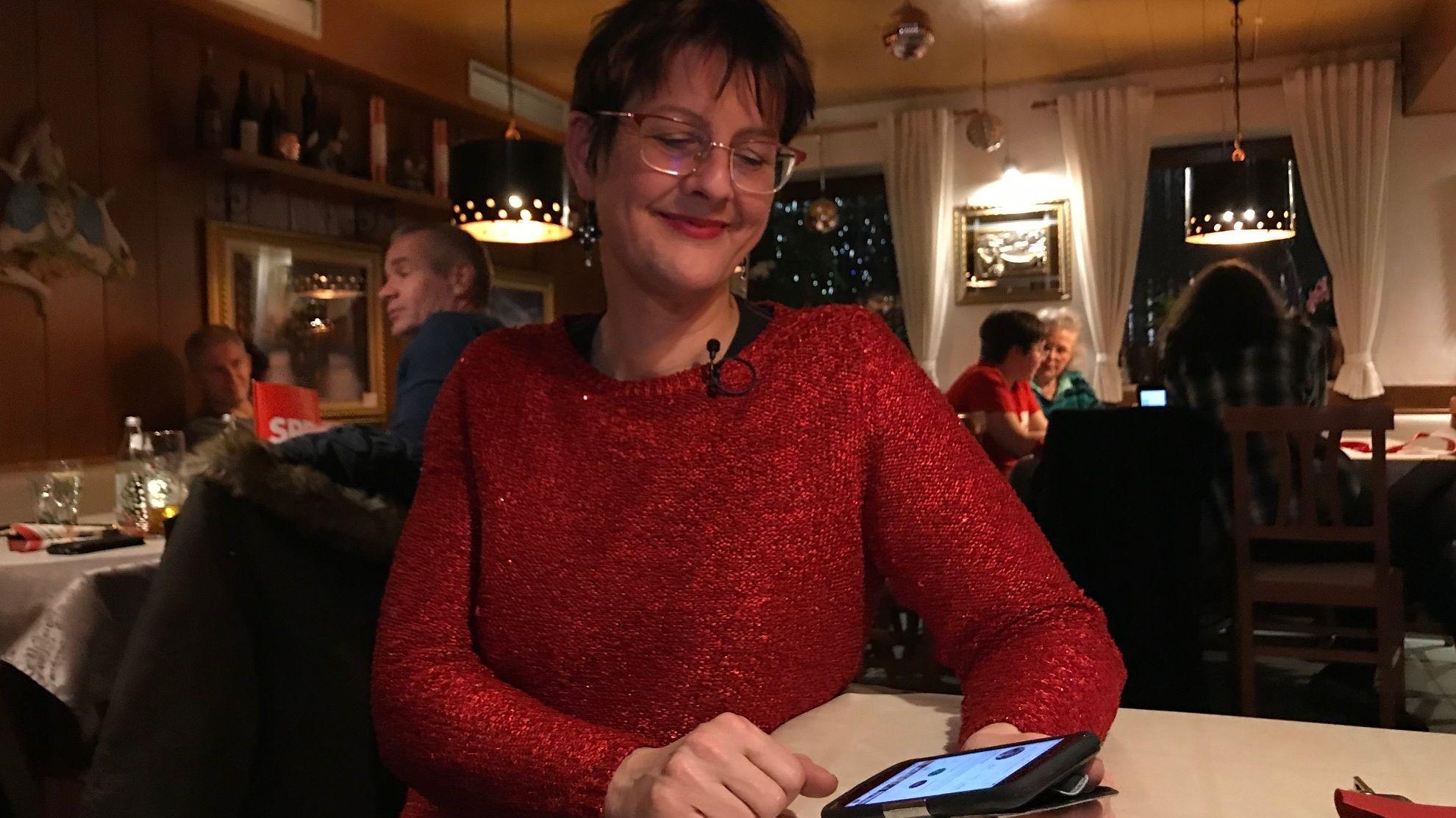 Angelika Kölbl mit dem Smartphone in der Hand