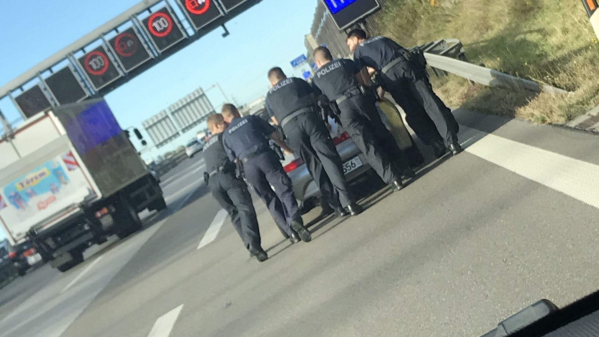 Polizeibeamte auf Seitenstreifen schieben ein liegengebeliebenes Auto
