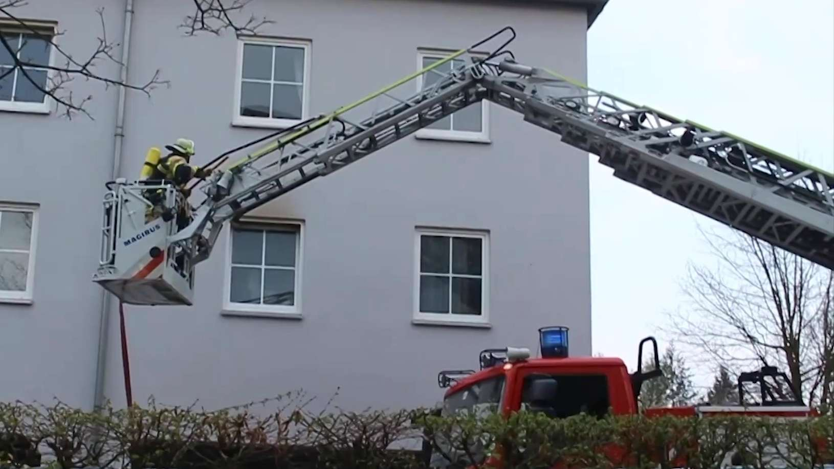 Ein Feuerwehrmann auf einer Drehleiter vor einem grauen Mehrfamilienhaus.