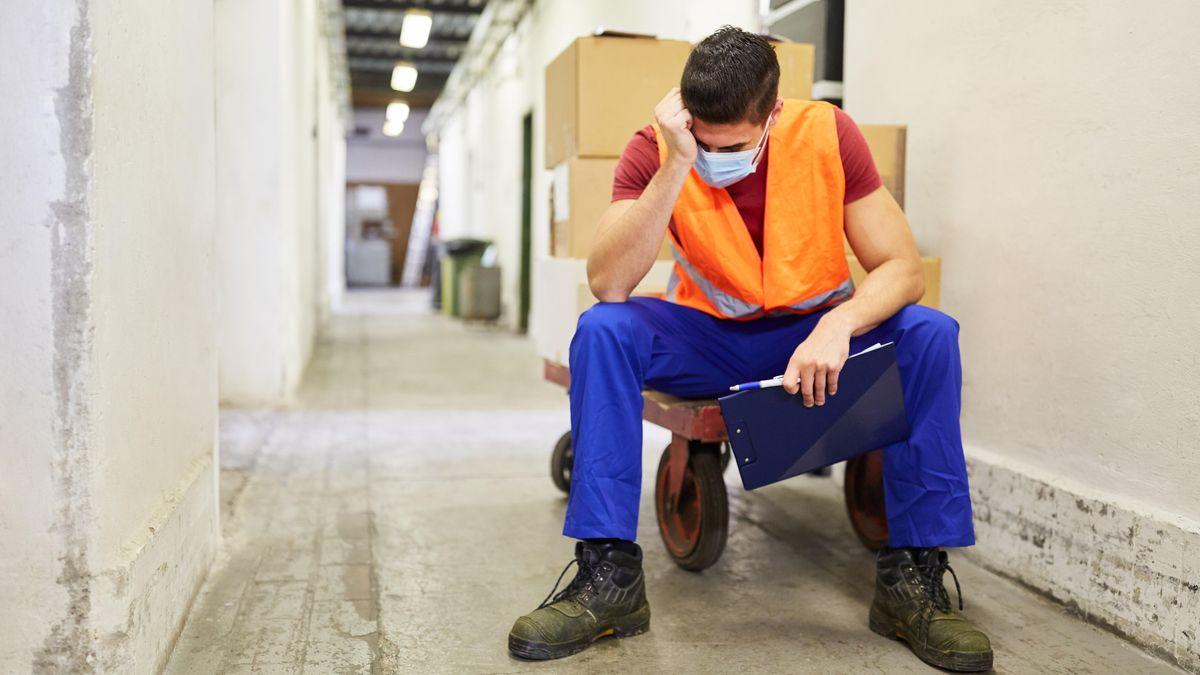 Ein erschöpfter Arbeiter mit Mundschutz in einem Warenlager