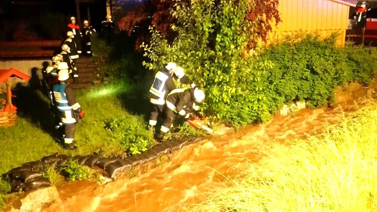 Feuerwehrmänner stehen an einem überfluteten Bach