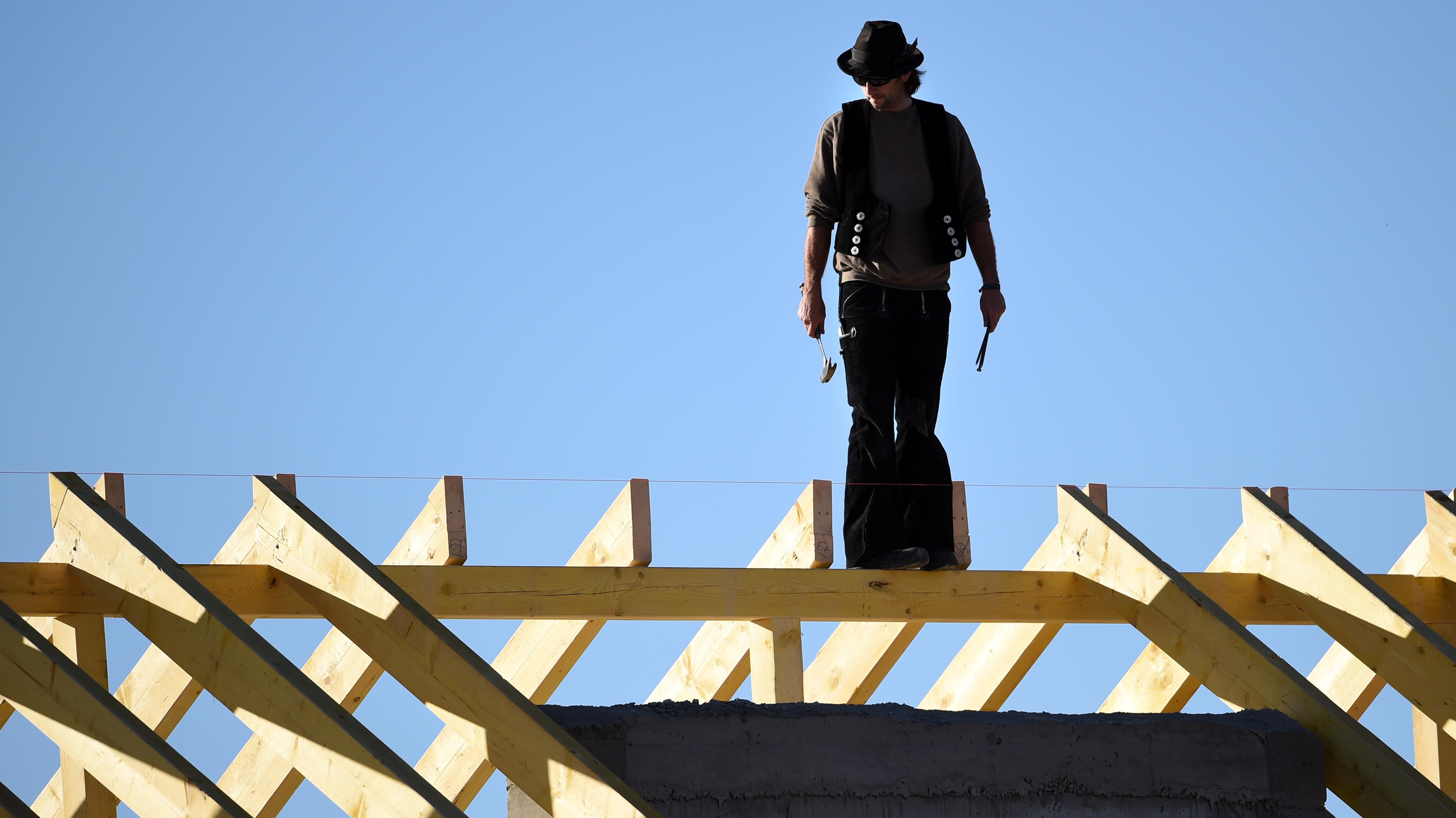 Symbolbild: Zimmermann auf Hausdach