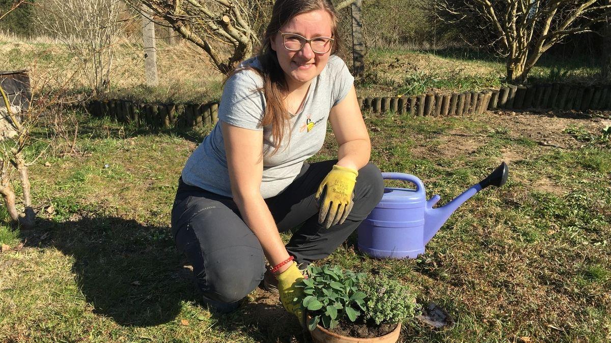 Stefanie Propp kniet in ihrem Garten vor einer Tonschüssel mit Kräutern, dahinter eine lilafarbene Gießkanne.