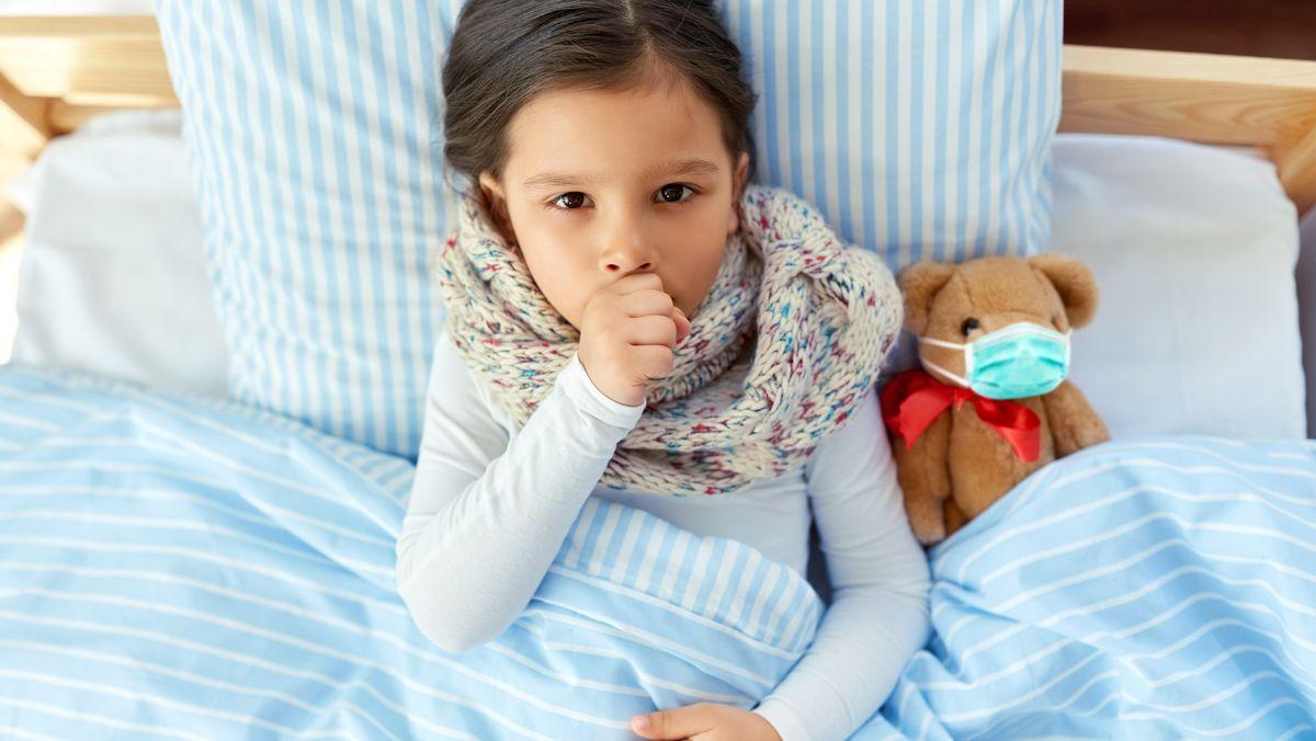 Krankes Mädchen im Bett hat einen Stoffbären an ihrer Seite, der eine Corona-Maske trägt (Symbolbild)