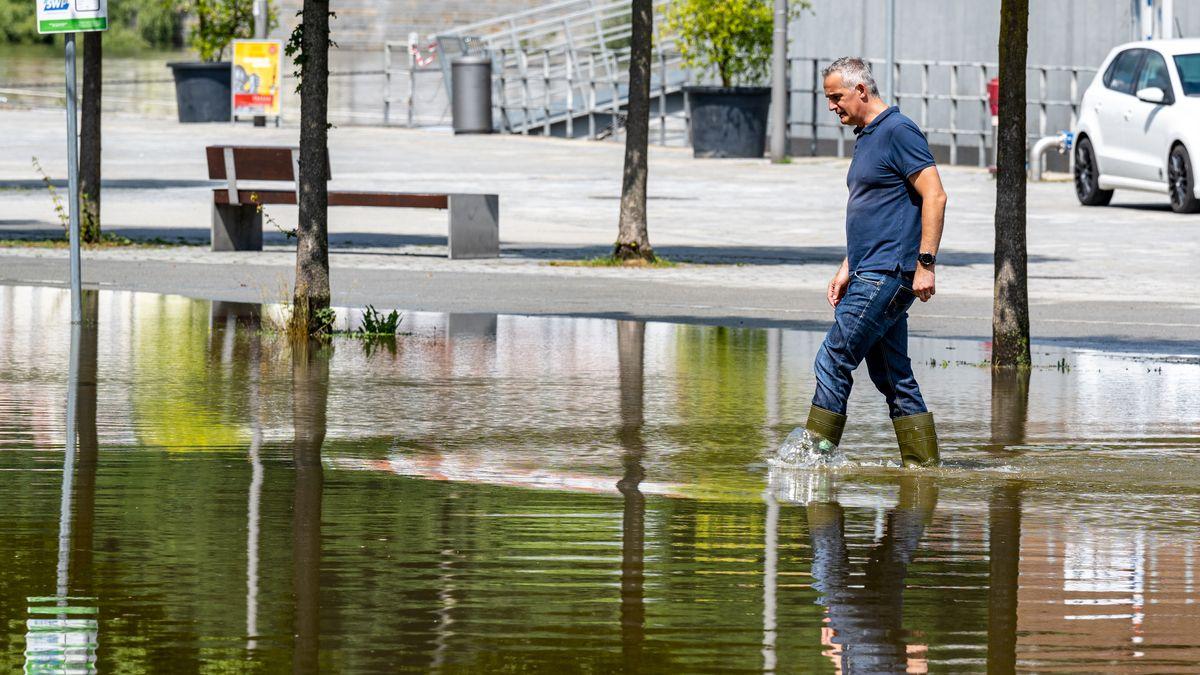Ein Mann watet in Passau durch Hochwasser (Symbolbild)