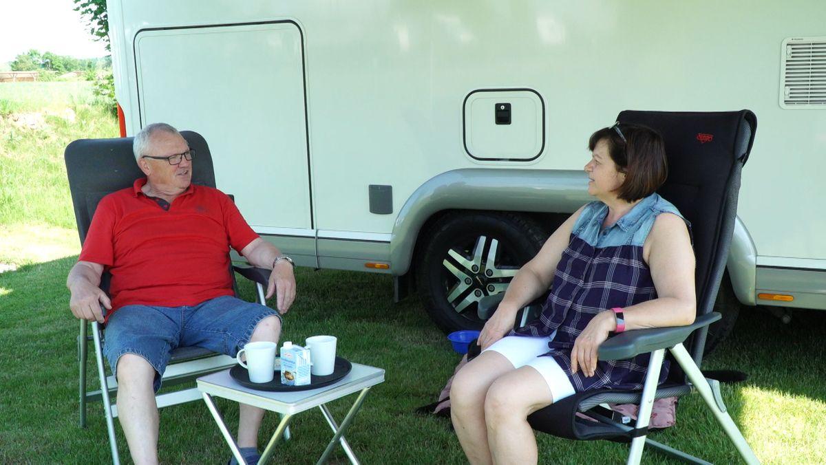 Zwei Personen auf Camping-Stühlen vor einem Wohnmobil