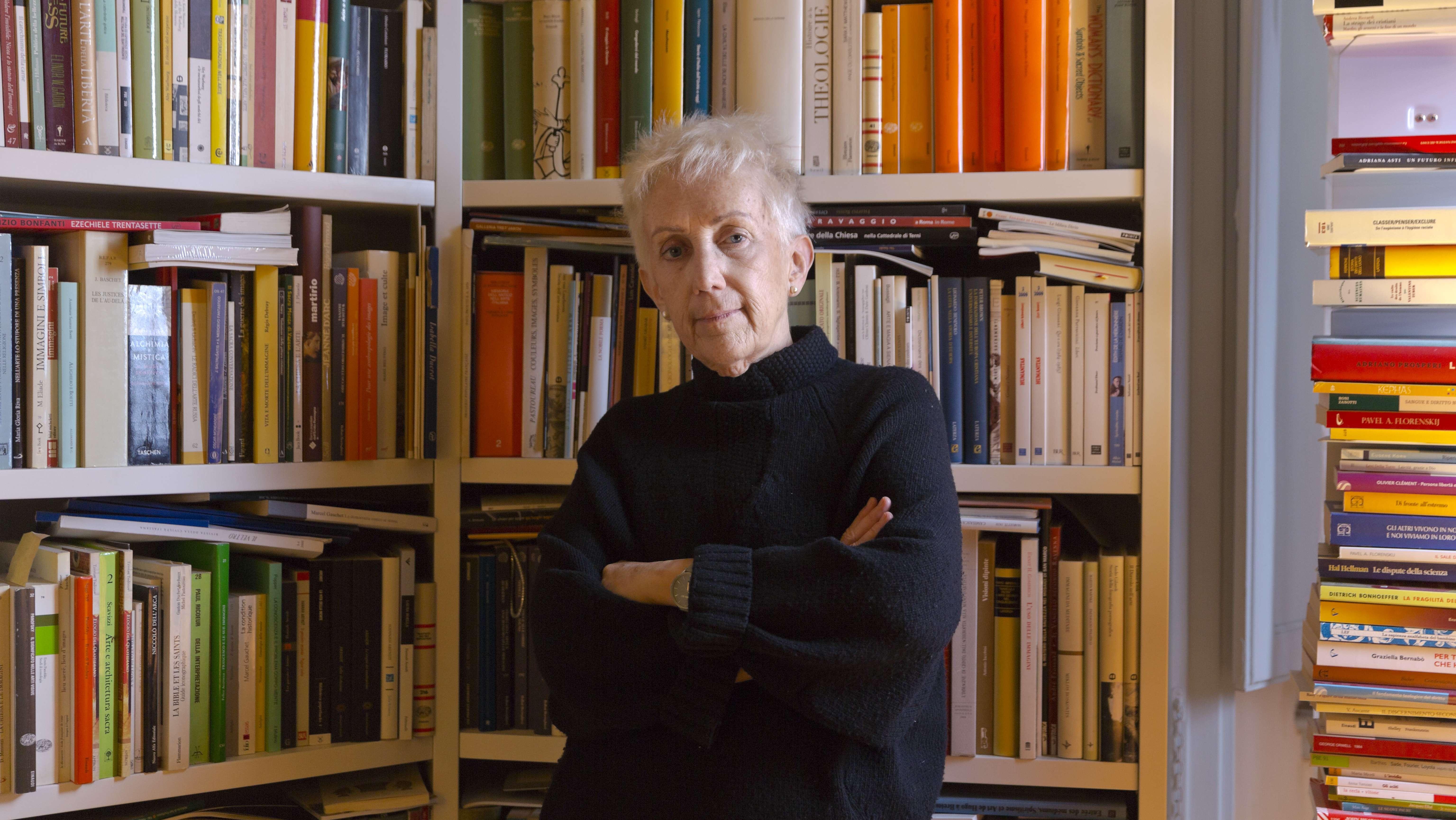 """Lucetta Scaraffia, Gründerin und Herausgeberin der vatikanischen Frauenzeitschrift """"Donne Chiesa Mondo"""", steht mit verschränkten Armen vor ihrem Bücherregal."""