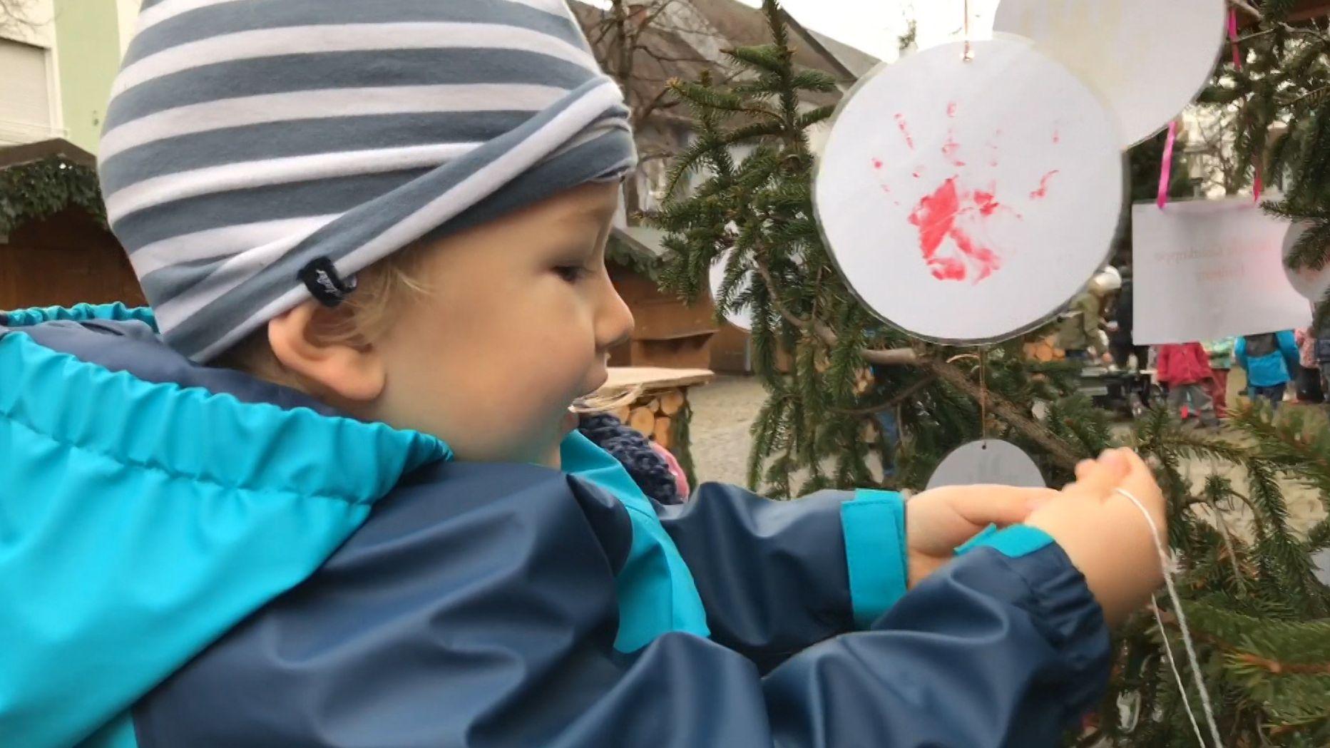 Ein kleines Kind schmückt einen der Bäume