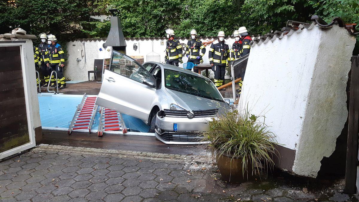 Ein graues Auto hängt mit verbogener Front über einem abgedeckten Pool. Feuerwehrleute stehen in zwei Gruppen um den Pool herum.