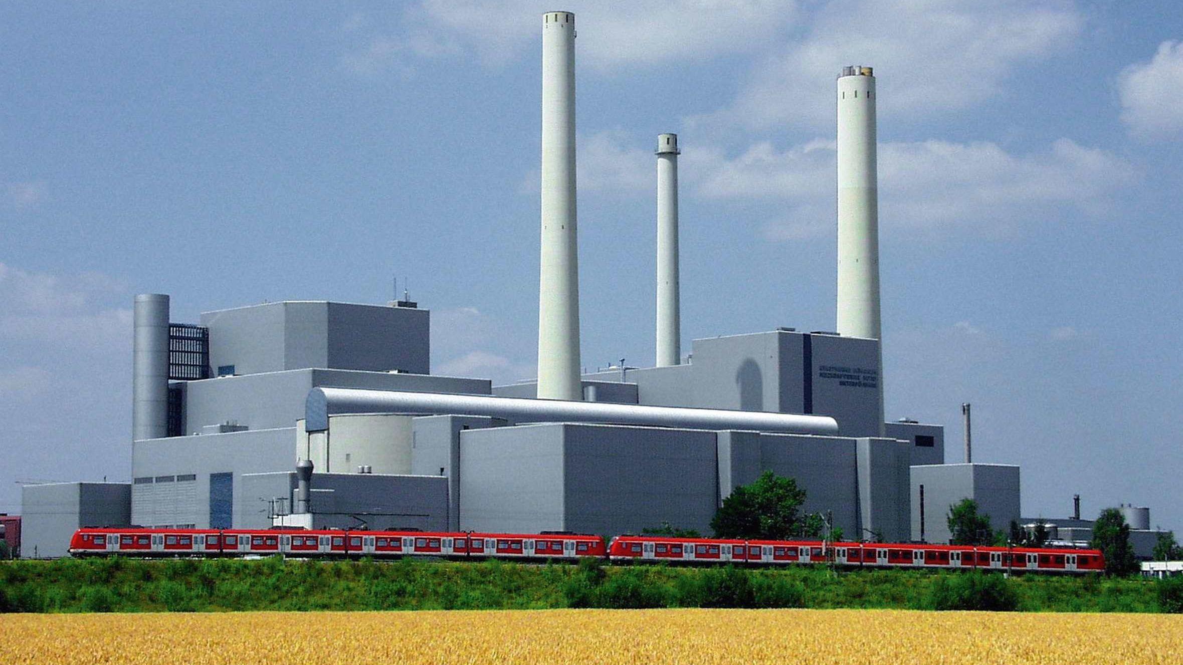 Heizkraftwerk München Nord im Sommer. Im Vordergrund fährt eine S-Bahn. Ein Getreidefeld ist im Vordergrund.