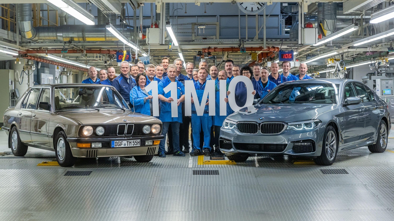 """BMW-Mitarbeiter stehen zwischen zwei Autos und halten die """"11Mio"""" hoch"""