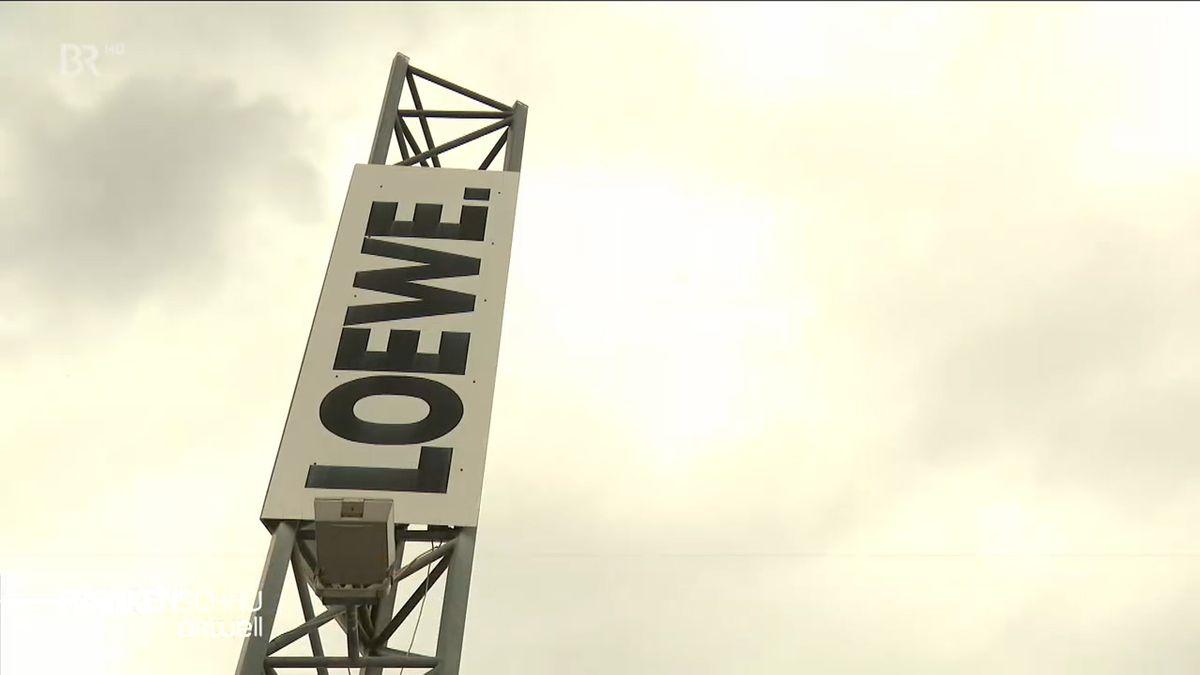 """Ein Masten ragt in die Höhe, auf dem der Schriftzug """"Loewe"""" in großen, schwarzen Buchstaben zu lesen ist."""
