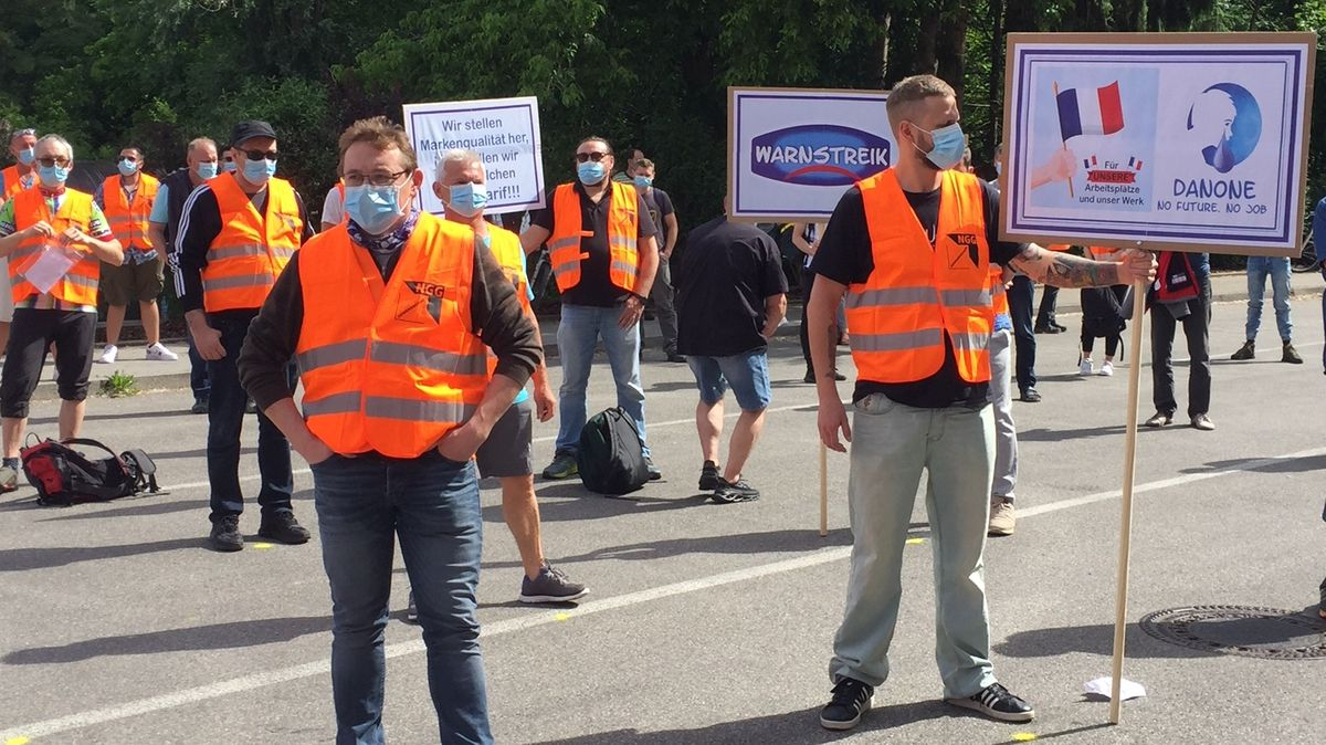 Mitarbeiter des Danone-Werks in Rosenheim stehen in Warnwesten und mit Mund-Nasen-Schutz auf der Straße und streiken.