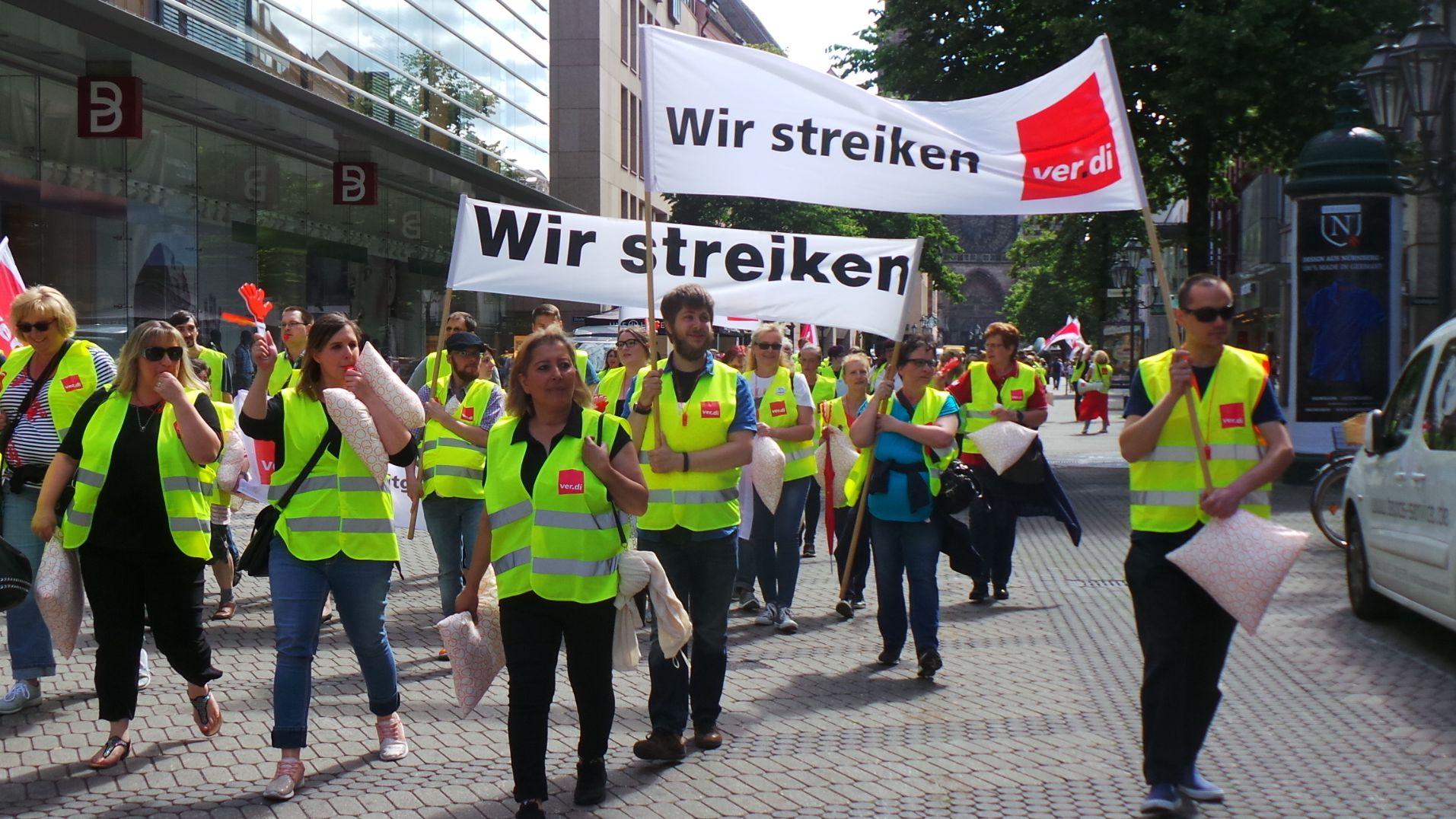 """Beschäftigte streiken, sie zeigen Banderolen mit der Aufschrift """"Wir streiken"""", zu sehen ist außerdem ein Verdi-Logo."""