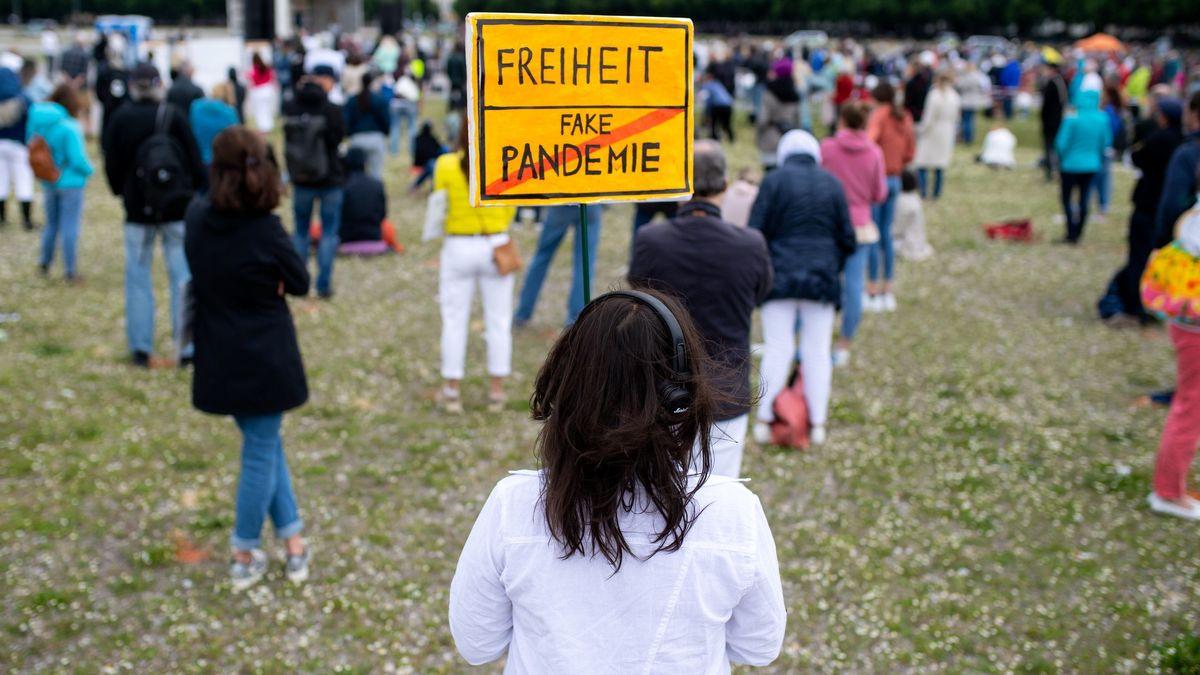 """30.05.2020, Bayern, München: Eine Teilnehmerin einer Demonstration gegen die Anti-Corona-Maßnahmen der Politik steht auf der Theresienwiese und hält ein Schild mit der Aufschrift """"Freiheit / Fake Pandemie"""" in den Händen."""