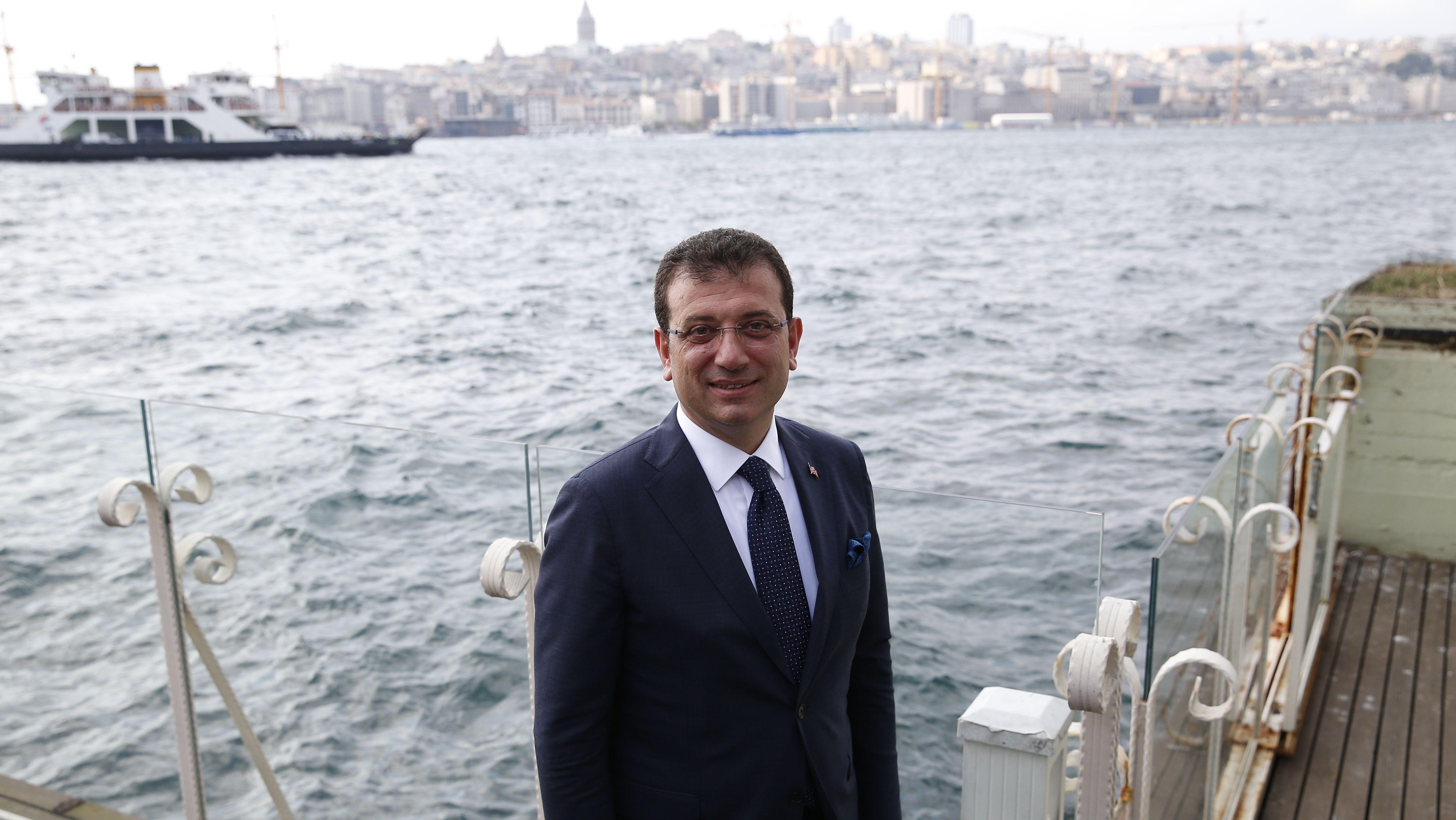 Istanbuls Bürgermeister Ekrem İmamoğlu posiert freundlich lächelnd im Anzug für ein Foto. Im Hintergrund sind der Bosporus und Istanbul zu sehen.