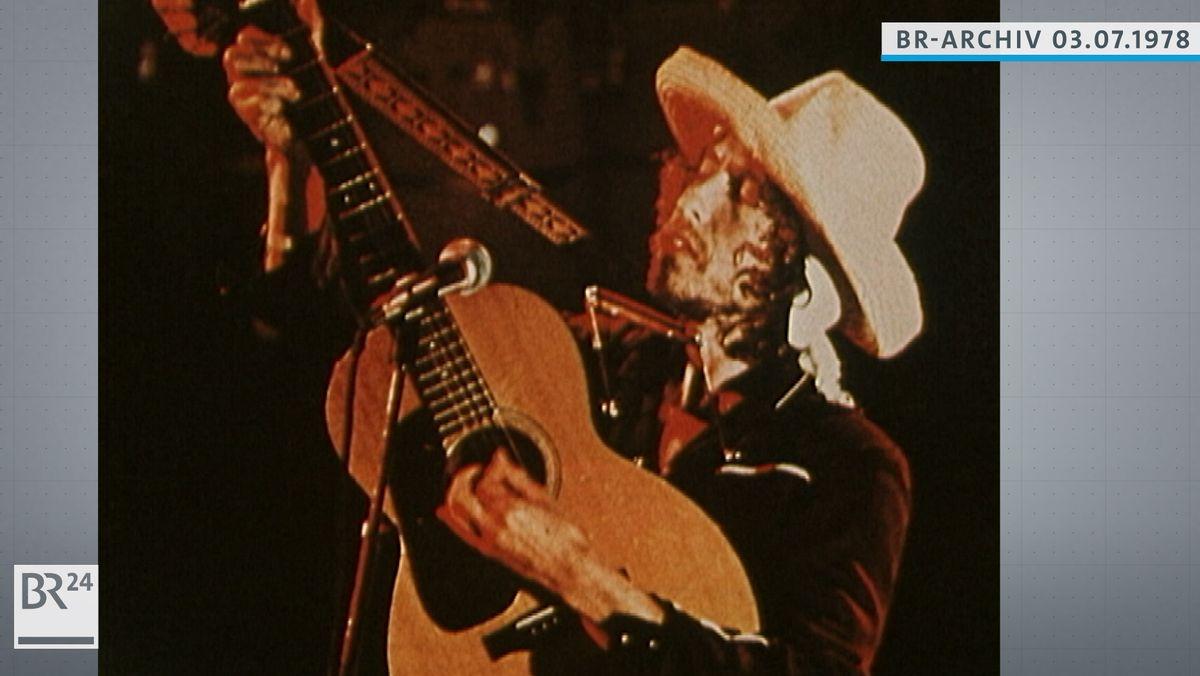 Foto Bob Dylan mit Gitarre und Mundharmonika