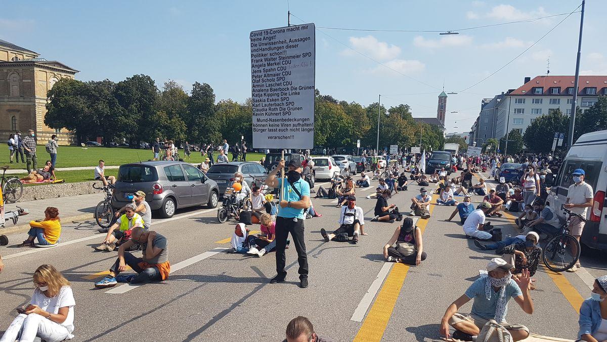 Demonstrationszug auf der Gabelsberger Straße kommt ins Stocken, Teilnehmer setzen sich hin.