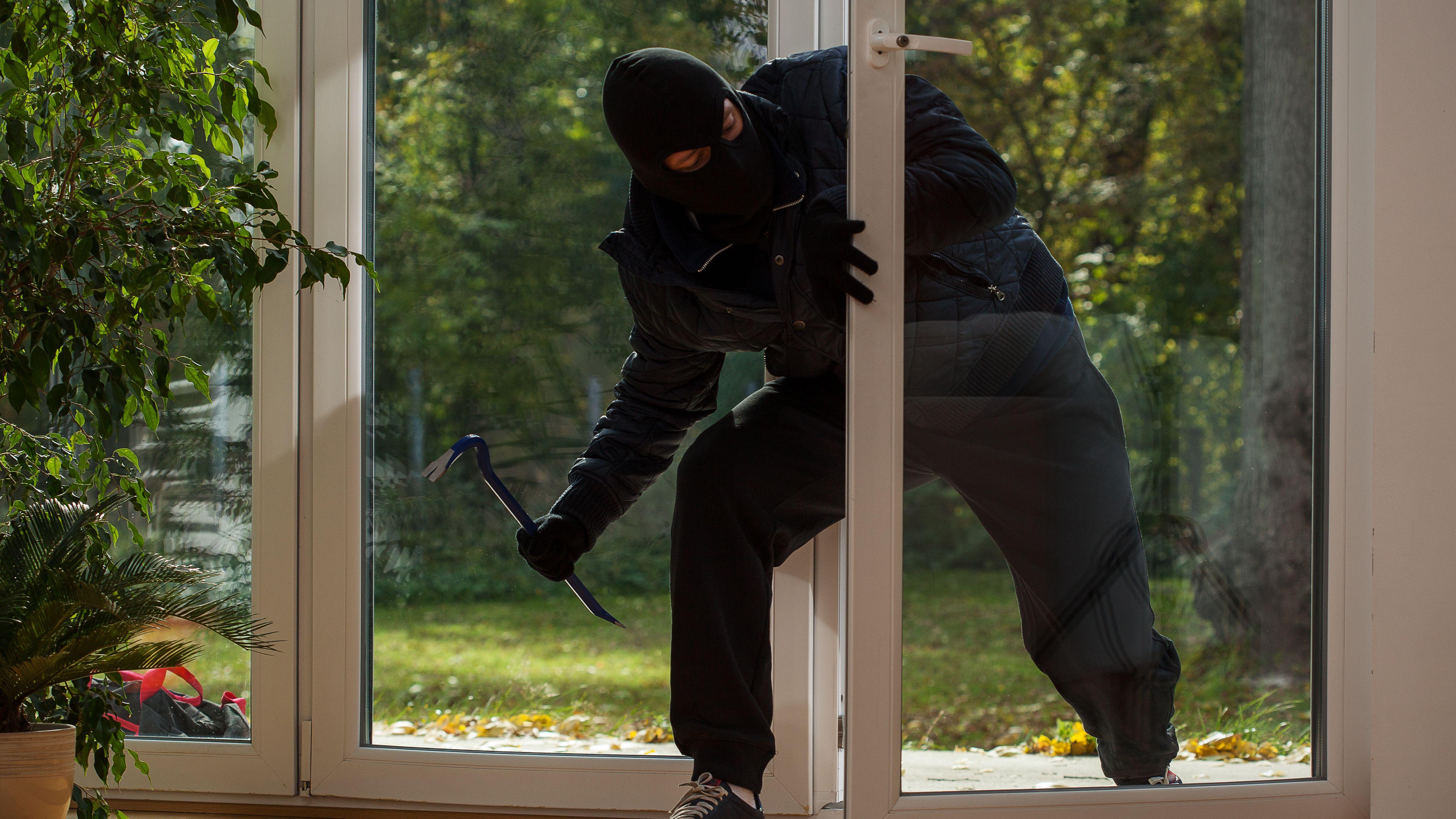 Ein Einbrecher steigt über die Terassentür in eine Wohnung ein.