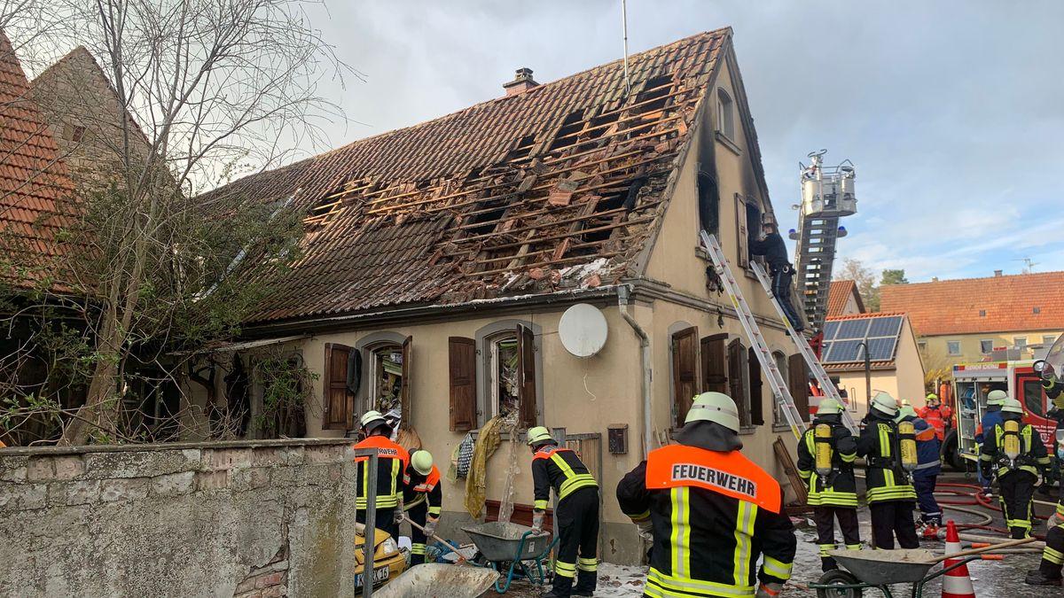 Feuerwehrleute räumen Schutt und Müll aus dem zuvor gelöschten Wohnhaus im Dettelbacher Ortsteil Schernau