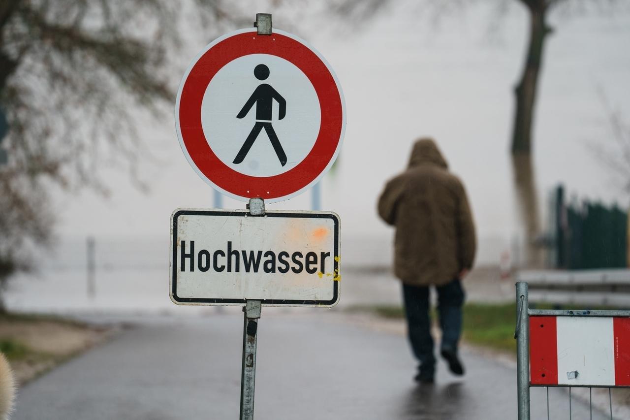 02.02.2021, Hessen, Eltville: Ein Mann geht hinter einem Schild mit der Warnung «Hochwasser» zum Rheinufer, das für den Verkehr wegen Hochwassers bereits gesperrt ist. Ergiebige Regenfälle lassen die Pegelstände der Flüsse in Hessen weiter steigen. Die Rheinfähre zwischen Ingelheim und Oestrich-Winkel hat ihren Betrieb wegen des Hochwassers eingestellt. Foto: Andreas Arnold/dpa +++ dpa-Bildfunk +++