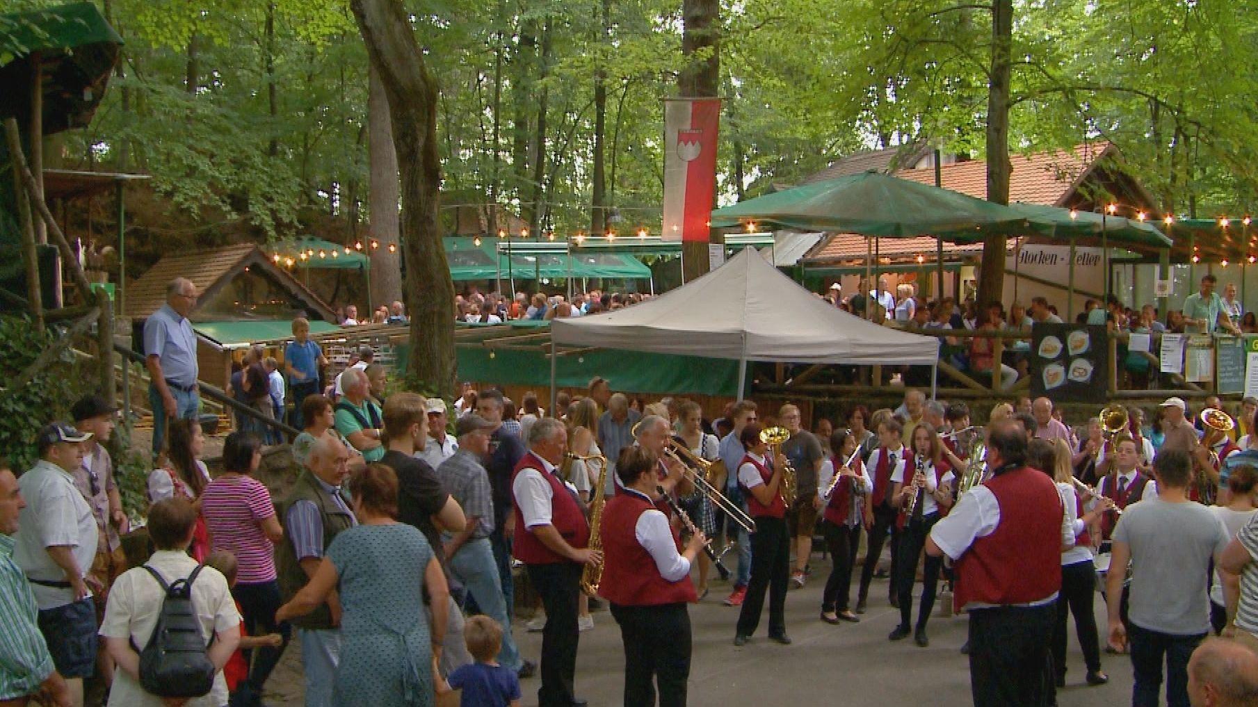 Zahlreiche Besucher und eine Blaskapelle sind auf einem Festplatz unter grünen Bäumen zu sehen.