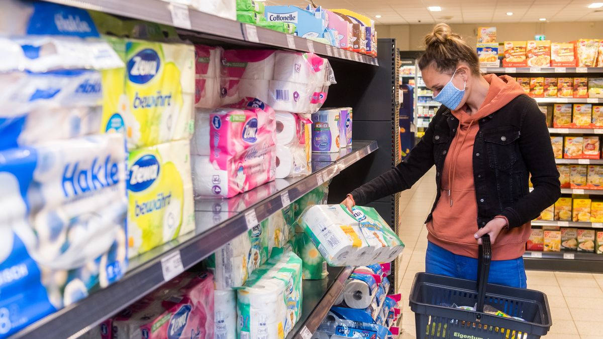 Eine Frau legt Toilettenpapier in ihren Einkaufskorb.