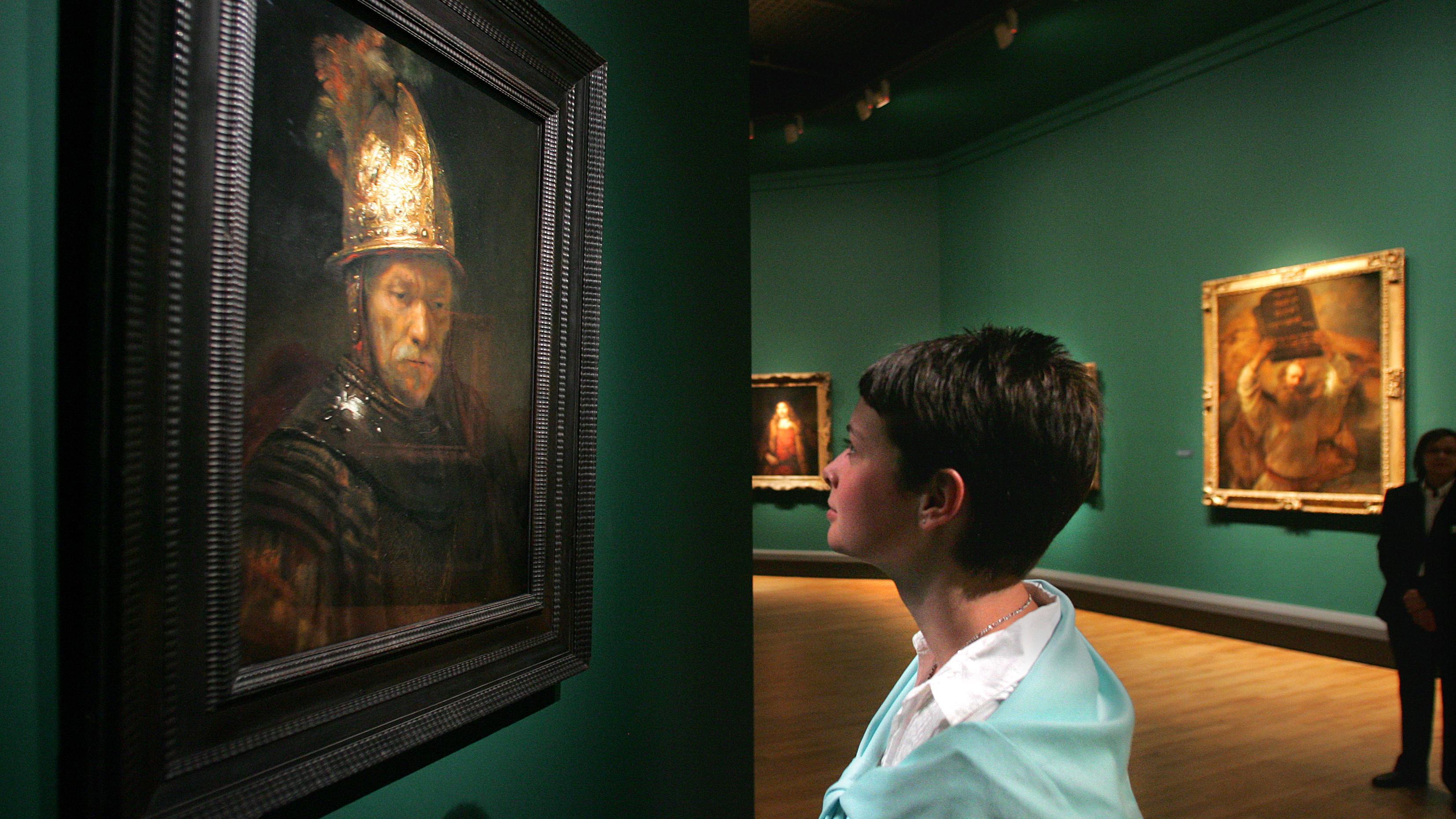 """Eine Frau im Museum schaut sich das Gemälde """"Der Mann ohne Helm an"""", von dem man lange dachte, es sei von Rembrandt. Es ist aber von einem seiner Schüler."""