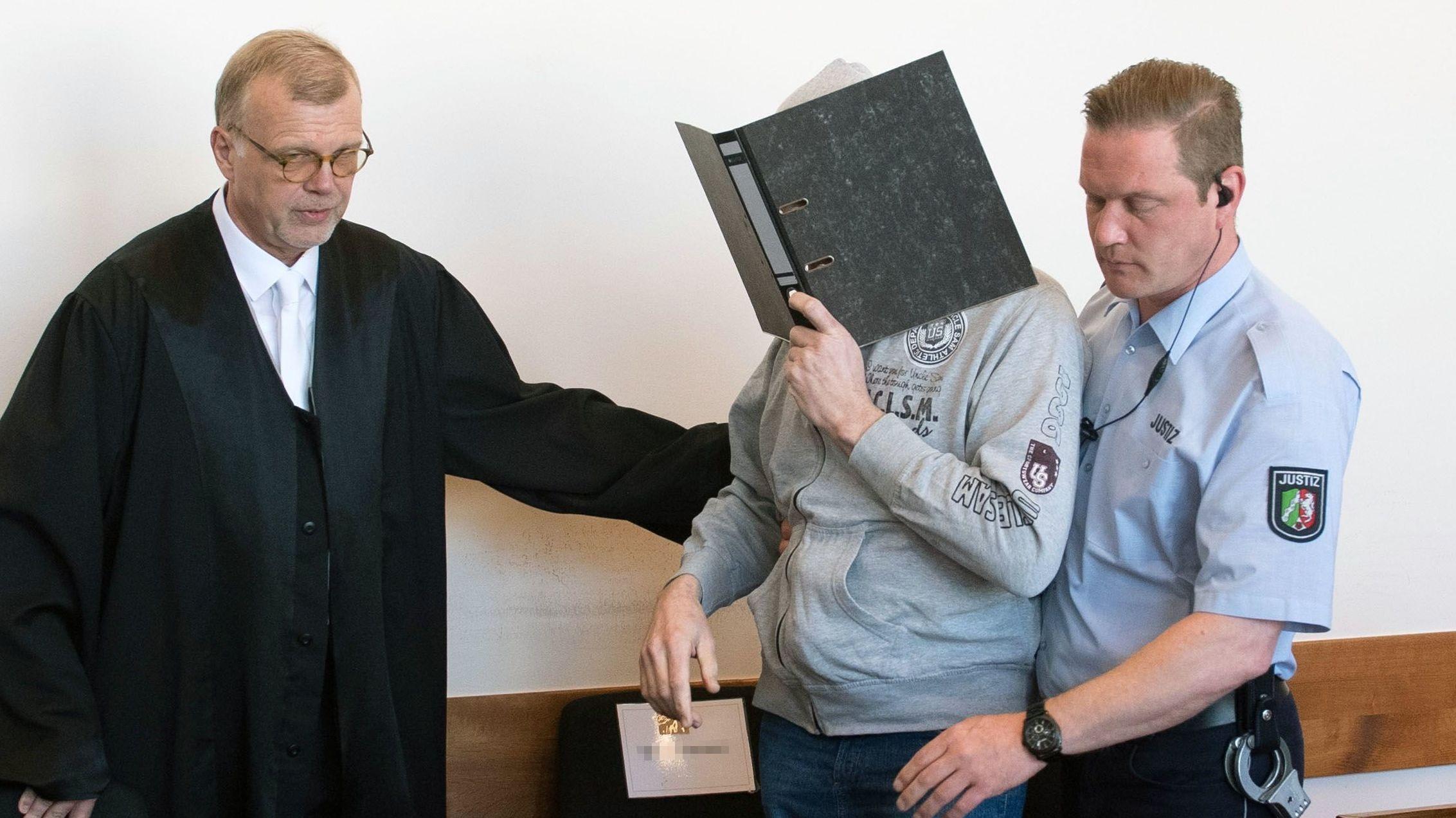 Der Angeklagte Andreas V. wird von einem Justizmitarbeiter in den Saal des Detmolder Landgerichtes geführt.
