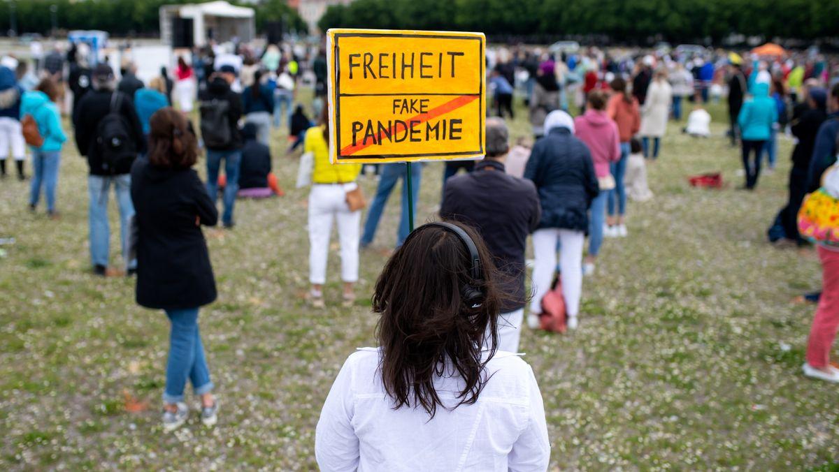 """Eine Teilnehmerin einer Demonstration gegen die Corona-Maßnahmen der Politik steht auf der Theresienwiese und hält ein Schild mit der Aufschrift """"Freiheit / Fake Pandemie"""" in den Händen."""