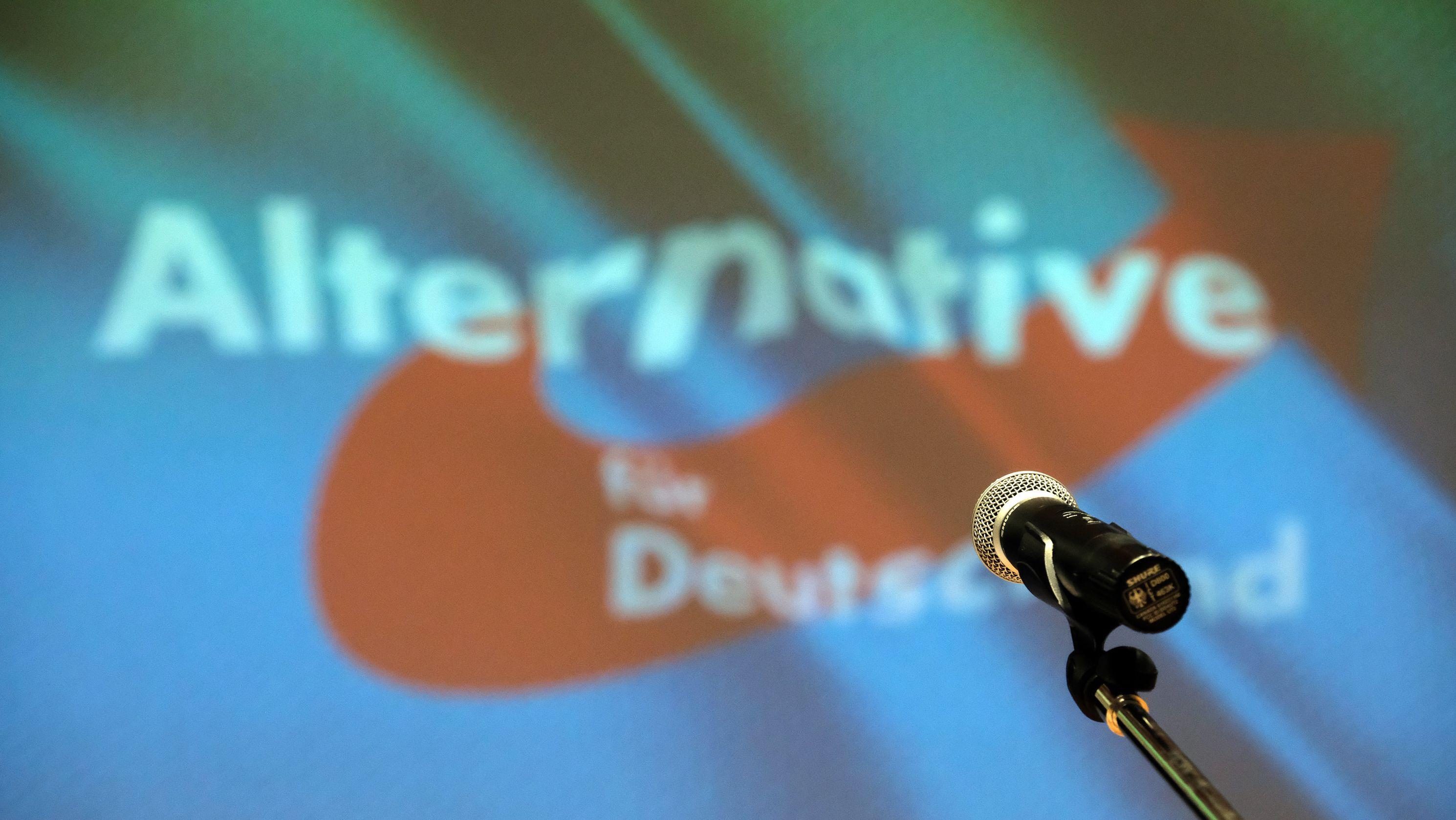 Die AfD in der Corona-Krise. Mikrofon vor Partei-Banner (Symbolbild)
