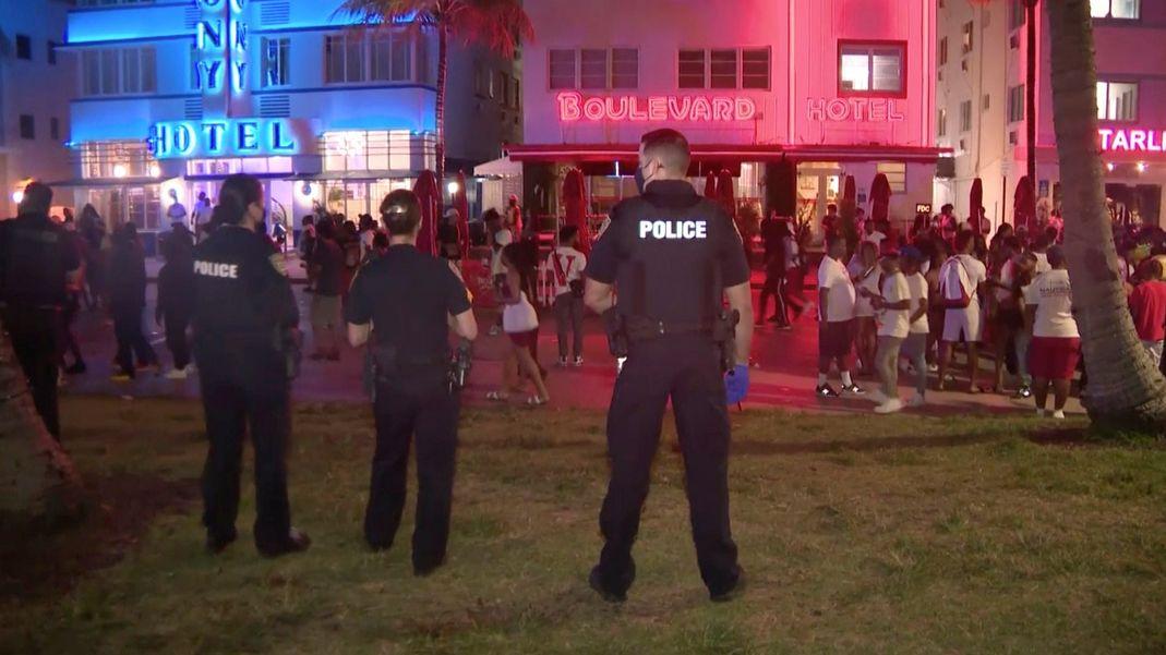 21.03.2021, USA, Miami: Polizisten stehen Wache während Menschen nach South Beach in Miami kommen.