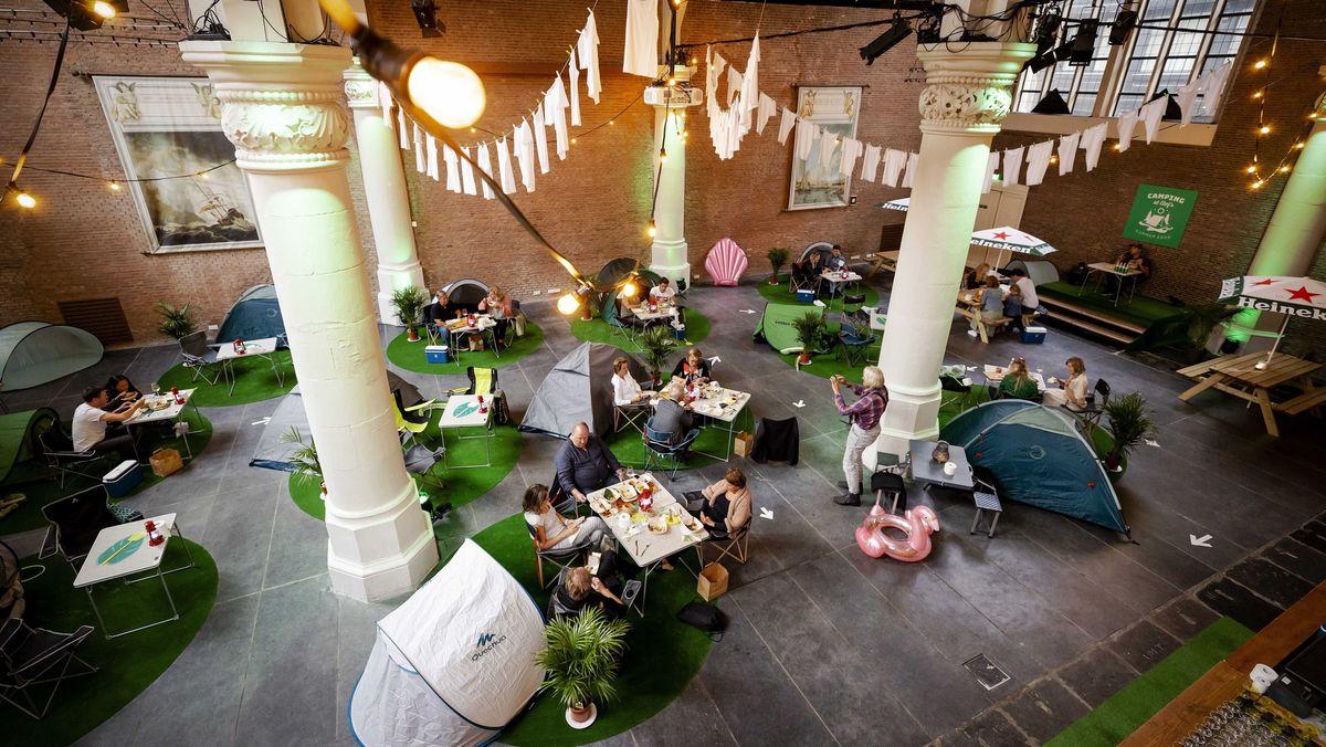 Gäste essen vor ihrem Zelt in einer ehemaligen Kirche.