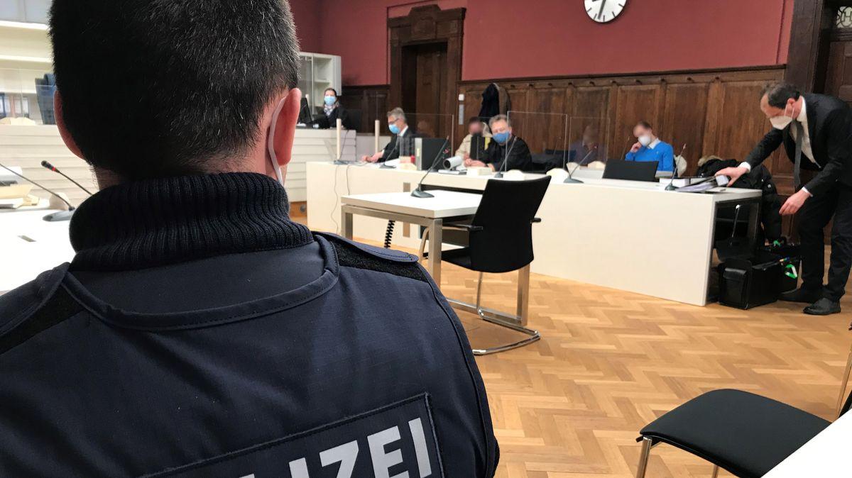 Polizist sitzt im Vordergrund und blickt auf die Anklagebank im Landgericht Amberg.