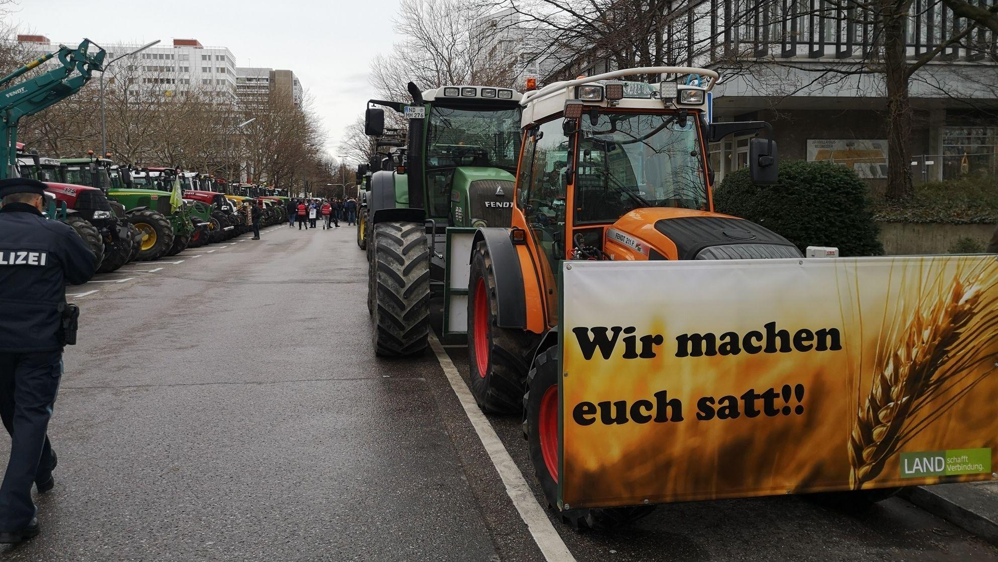 """Landwirte-Demo in München: Dabei hängt an einem Traktor ein Plakat mit der Aufschrift"""" Wir machen euch satt!!"""