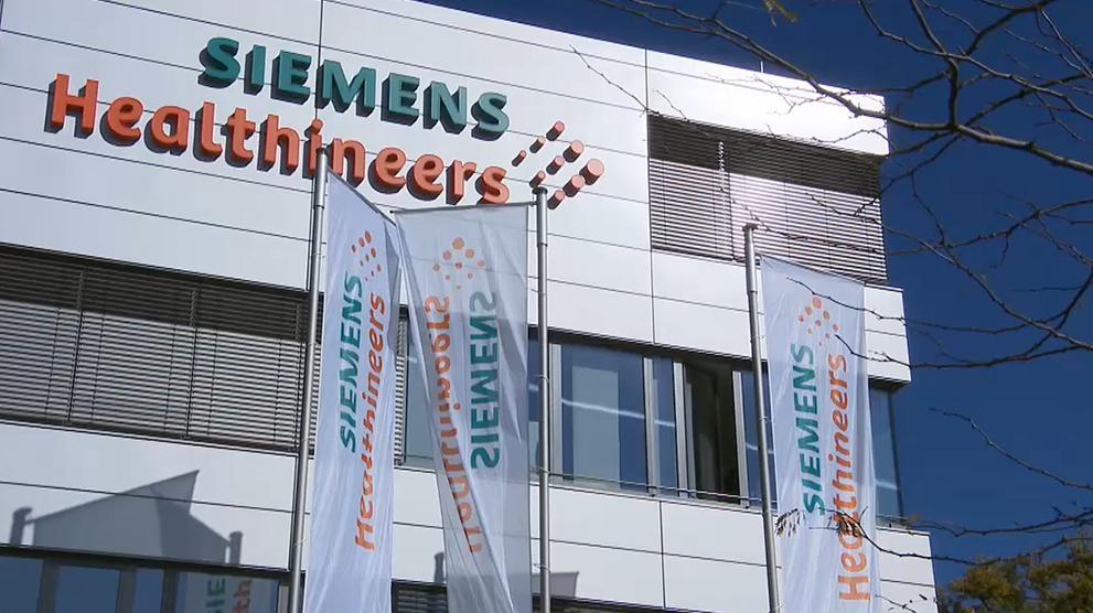 """Gebäude mit der Aufschrift """"Siemens Healthineers"""" und Fahnen davor."""
