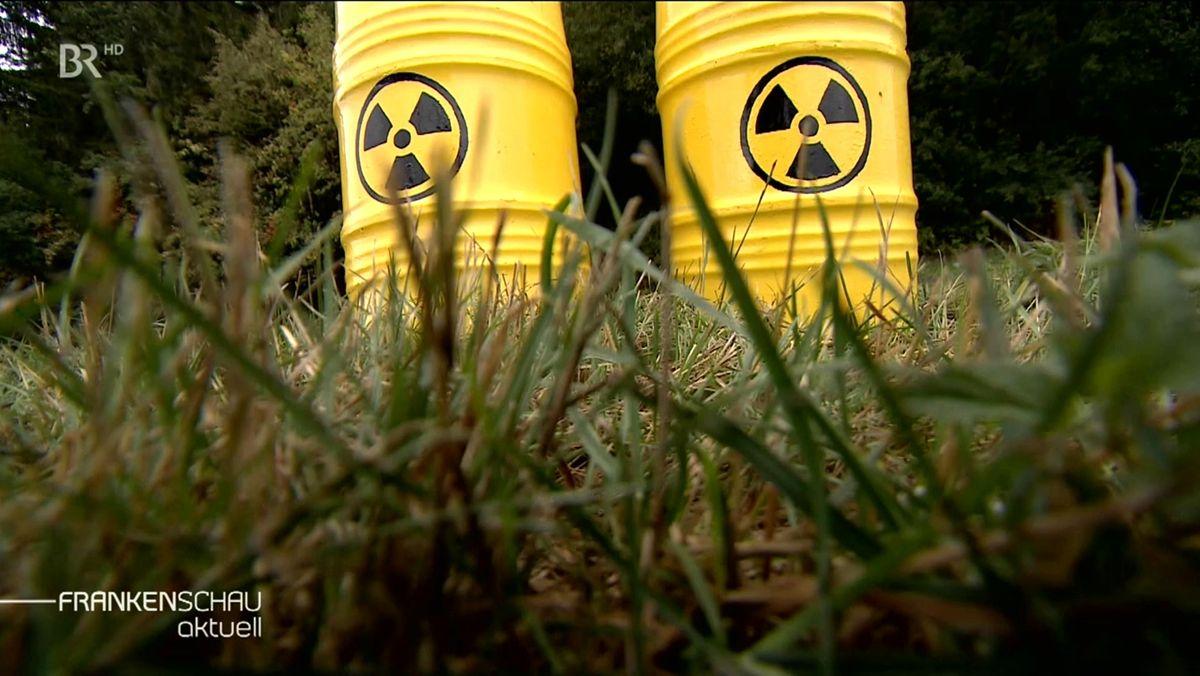 Zwei gelbe Fässer mit dem schwarzen Symbol für Atommüll stehen auf einer Wiese.