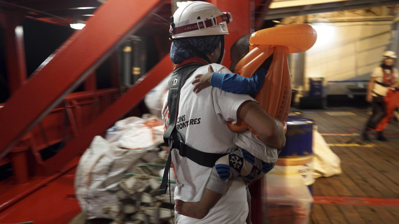 """10.09.2019, Mittelmeer: Ein Kleinkind wird auf dem Rettungsschiff """"Ocean Viking"""" von einem Arzt getragen."""