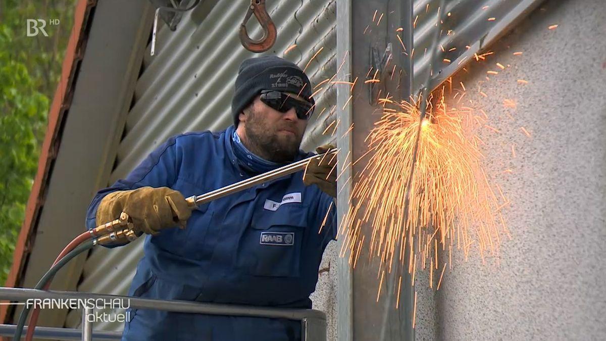 Ein Arbeiter trennt mit einem Schweißgerät einen Stahlträger von einer Befestigung.