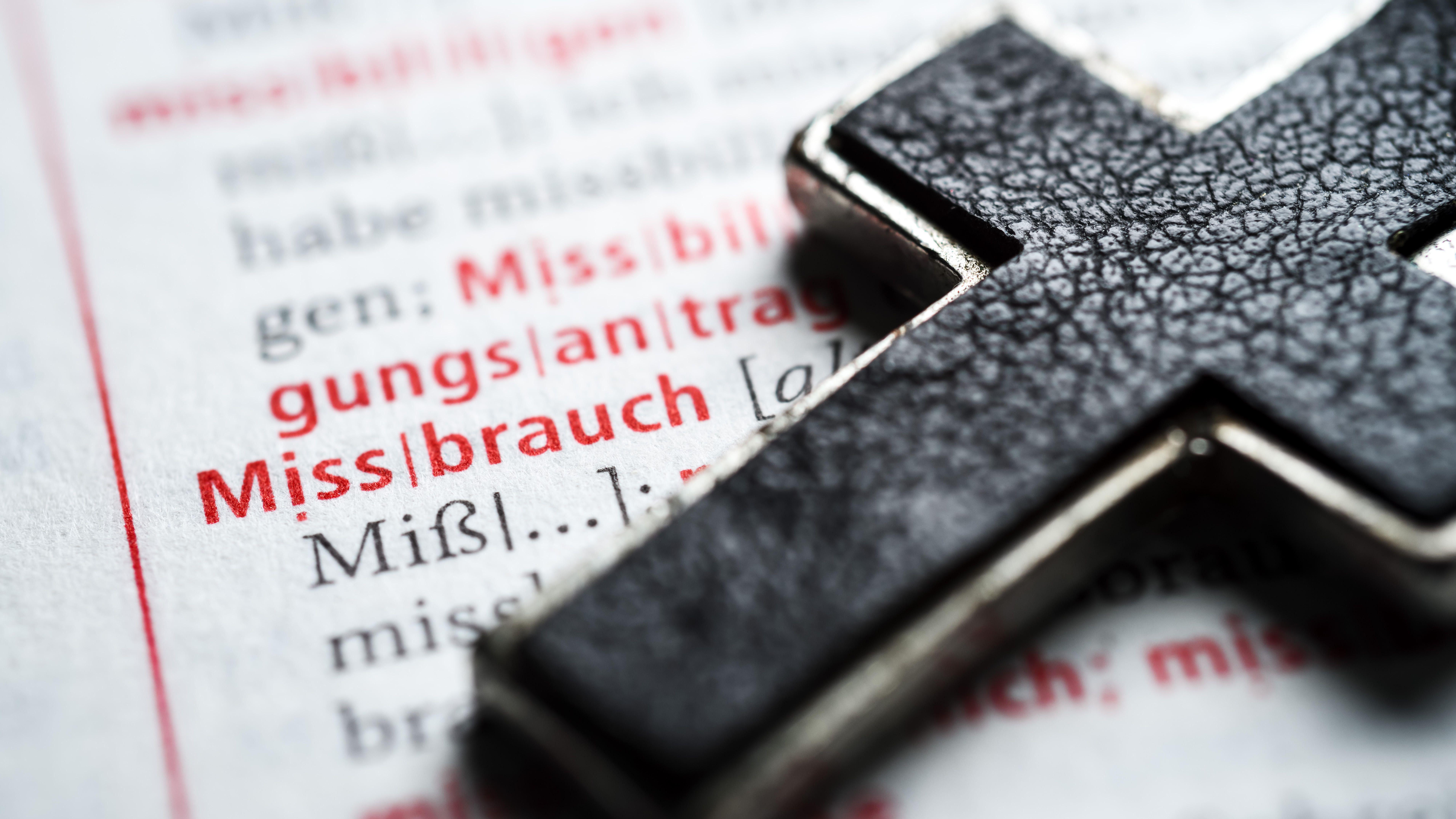 Ein ledernes Kreuz liegt auf einem Wörterbuch, das beim Wort Missbrauch aufgeschlagen ist.