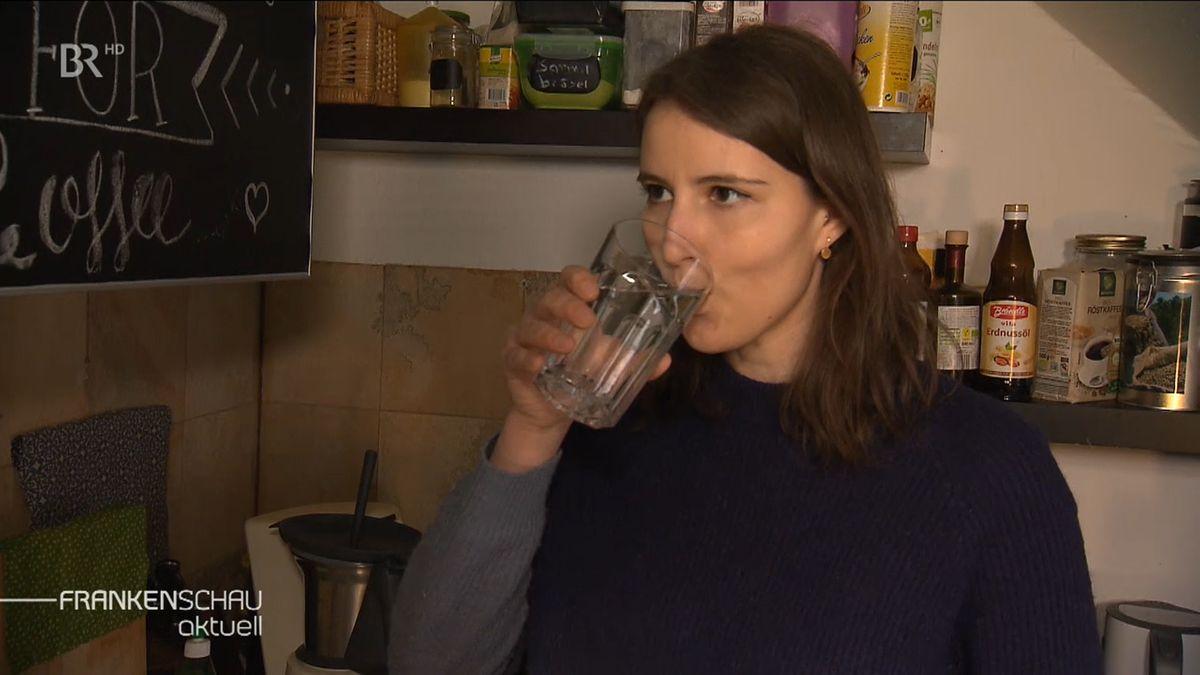 Junge Frau trinkt ein Glas Wasser.