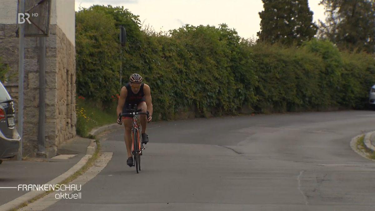 Der Triathlet Andreas Dreitz fährt mit seinem Rennrad auf einer Straße entlang, im Hintergrund eine Hecke und Bäume.