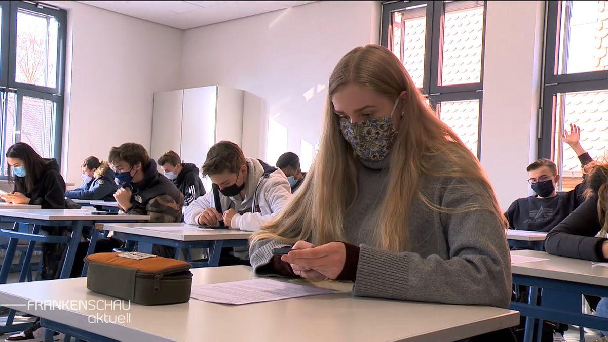 In einem Klassenzimmer sitzen Schüler an ihren Bänken und schauen auf ihr Smartphone.