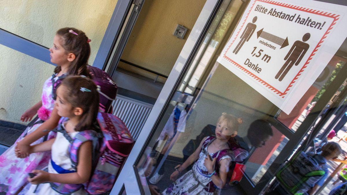 Schulkinder gehen durch eine Glastür, auf der ein Sicherheitshinweis zum Abstand halten steht.