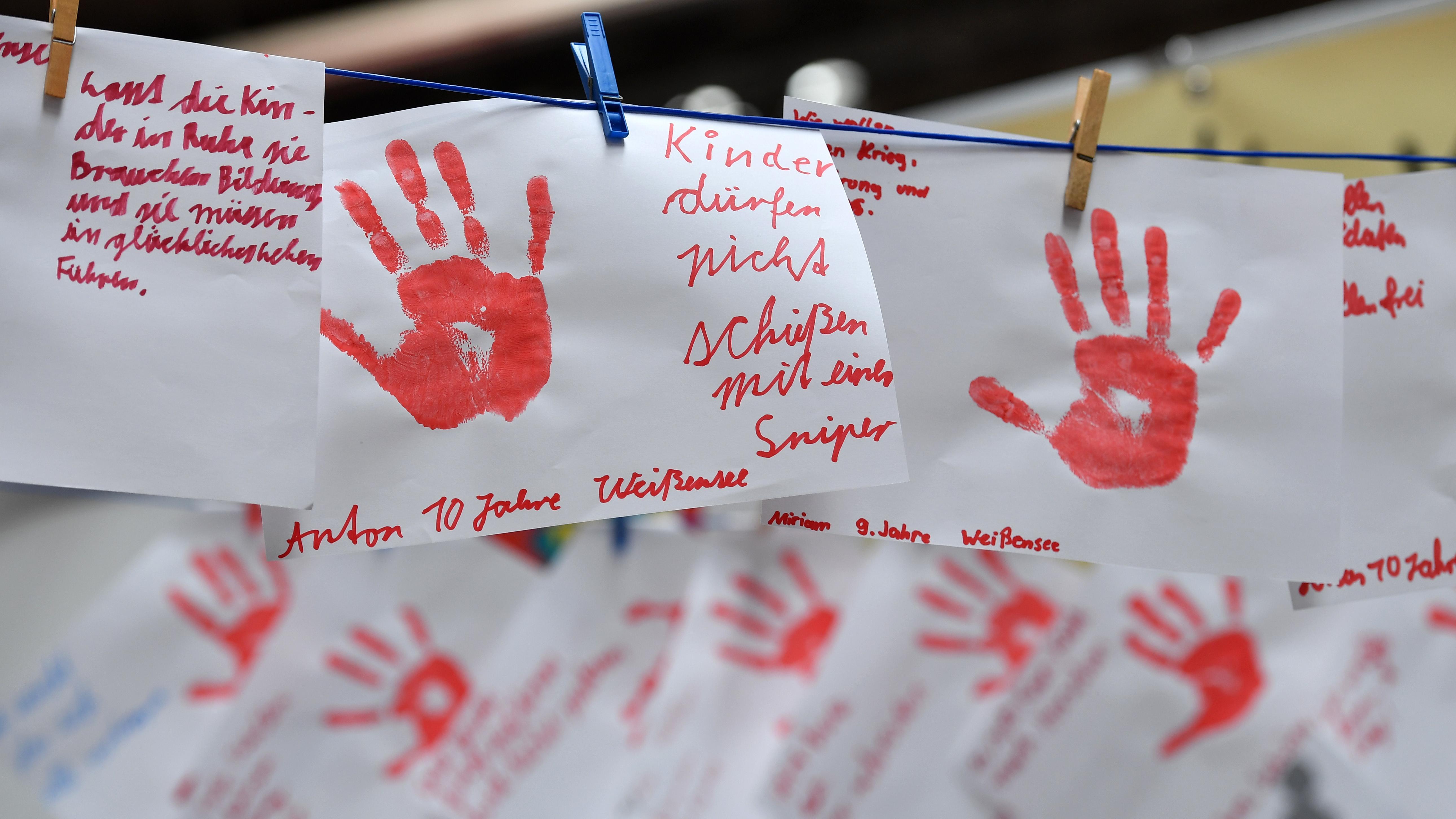 Blätter mit roten Handabdrücken und Gedanken von Kindern zum Thema Kindersoldaten hängen an einer Leine