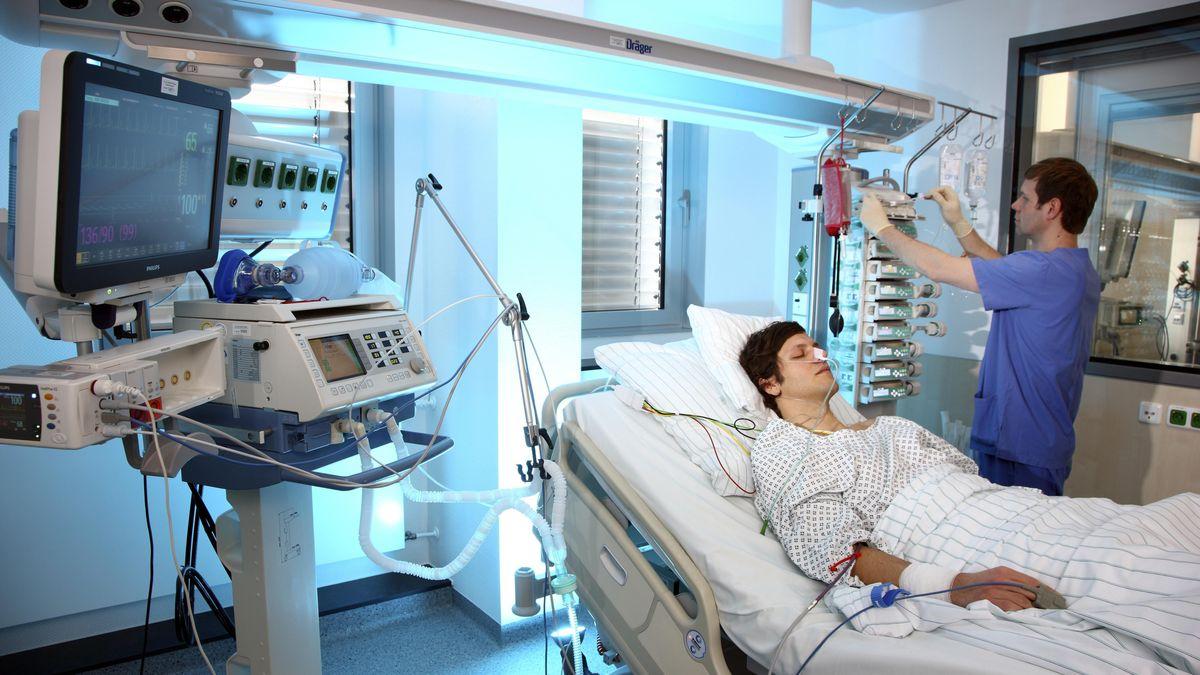 Intensivkrankenpfleger betreut Patient im Spezialbett