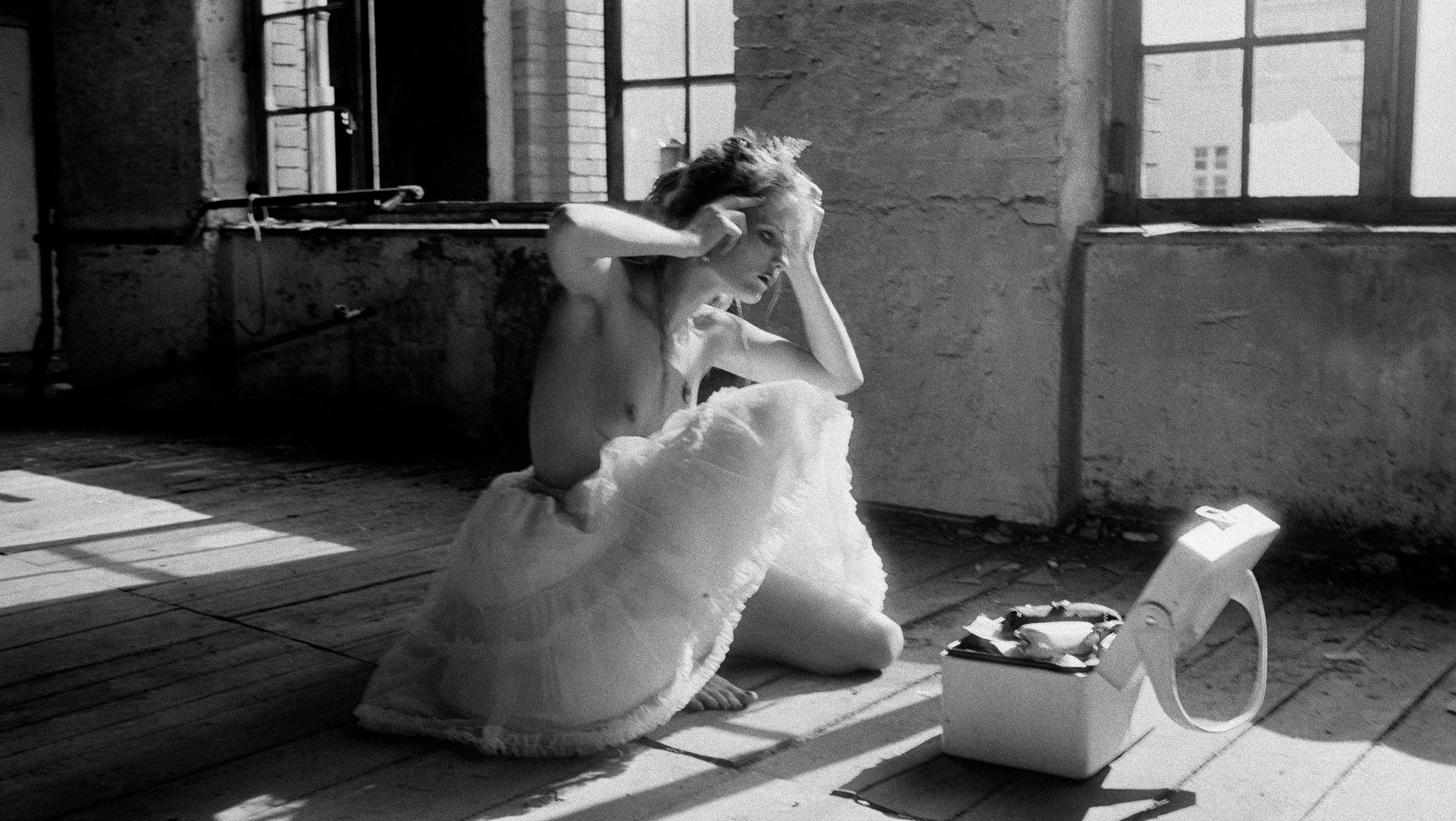 """Schwarz-weiß Foto von Marquardts Lieblingsmodel: Dominique """"Dome"""" Hollenstein kniet mit nacktem Oberkörper und weißem Tüllrock auf dem Boden in einem Stall."""