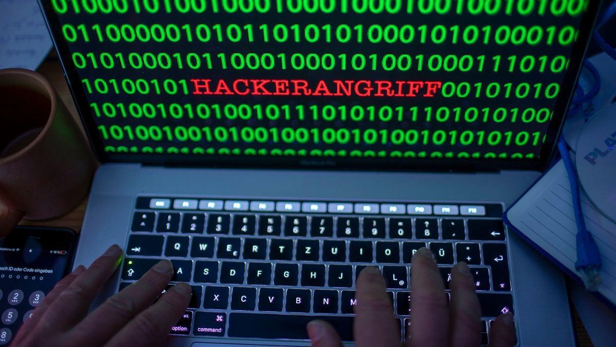 """Zwischen dem Binärcode auf einem Laptopmonitor ist das Wort """"Hackerangriff"""" zu sehen (Symbolbild)."""