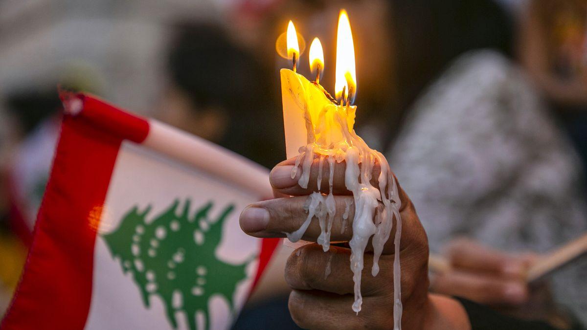 Eine mit Wachs bedeckte Hand hält Kerzen und eine Libanon-Flagge.