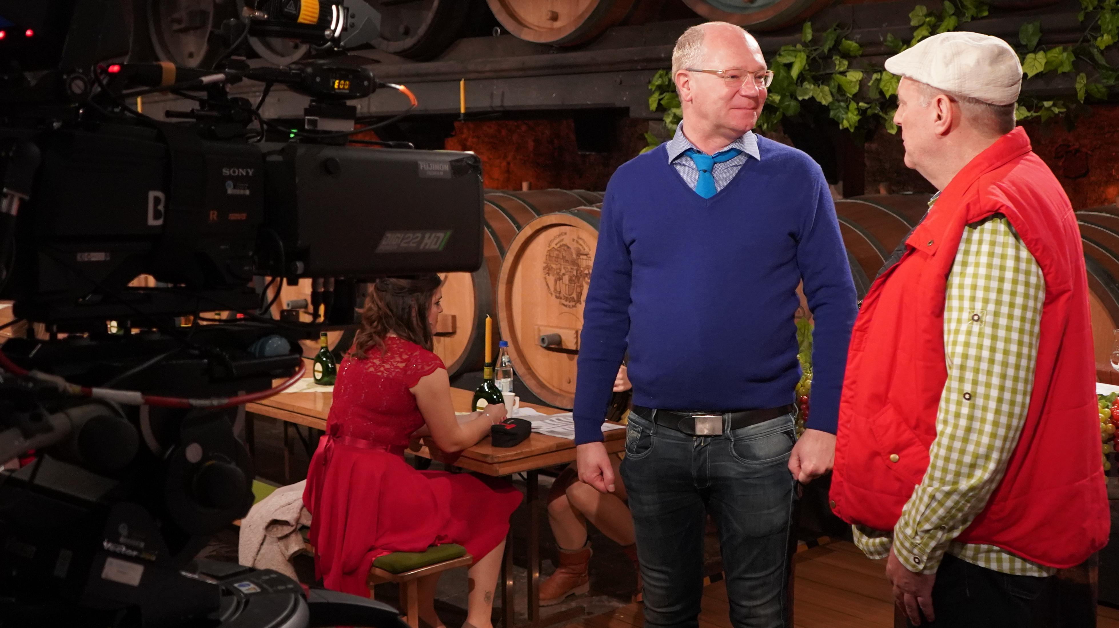 Showmaster Martin Rassau trägt Jeans, Pullover und Krawatte